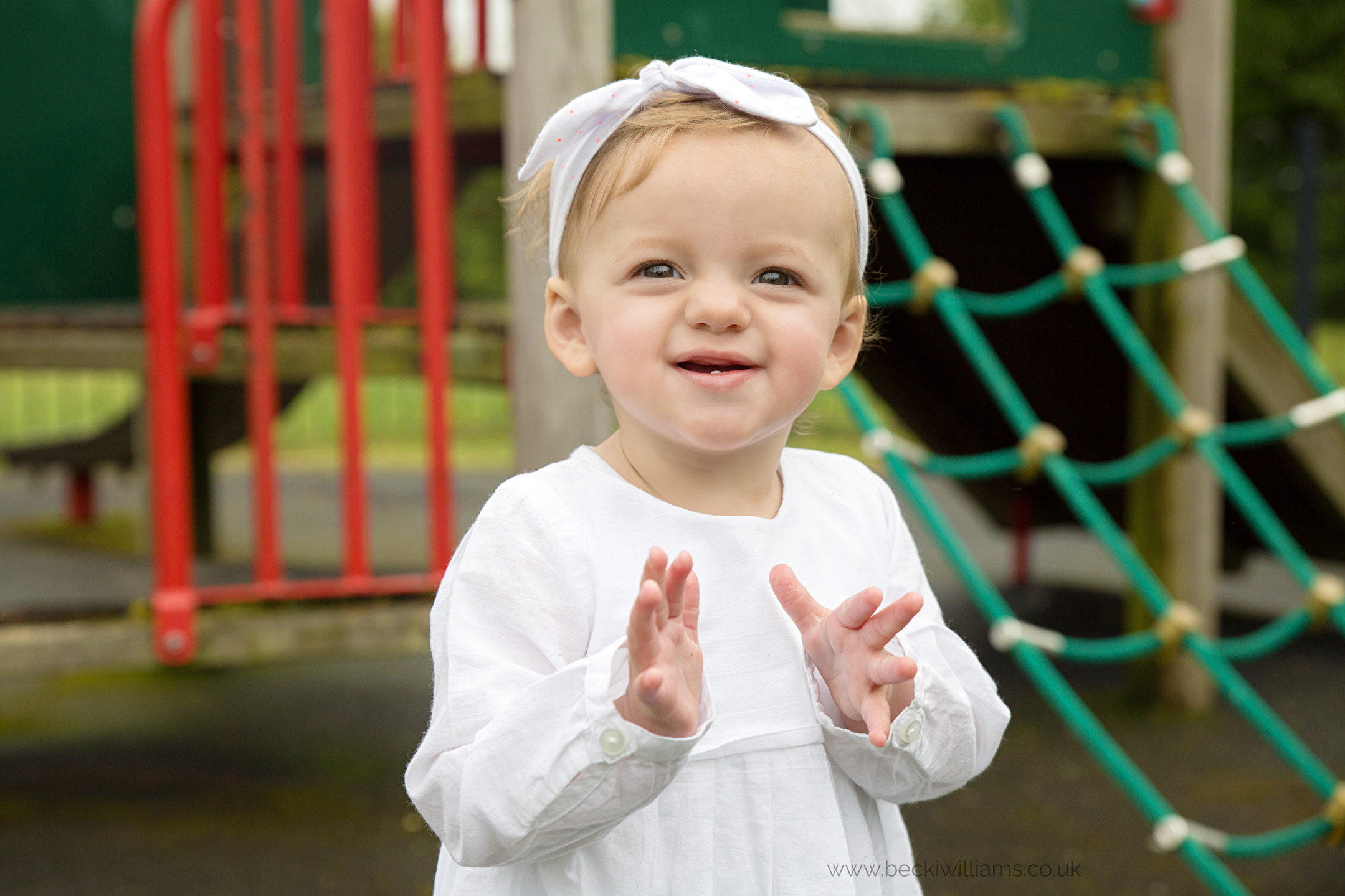 happy 1 year old in park while having professional photos taken in hitchin