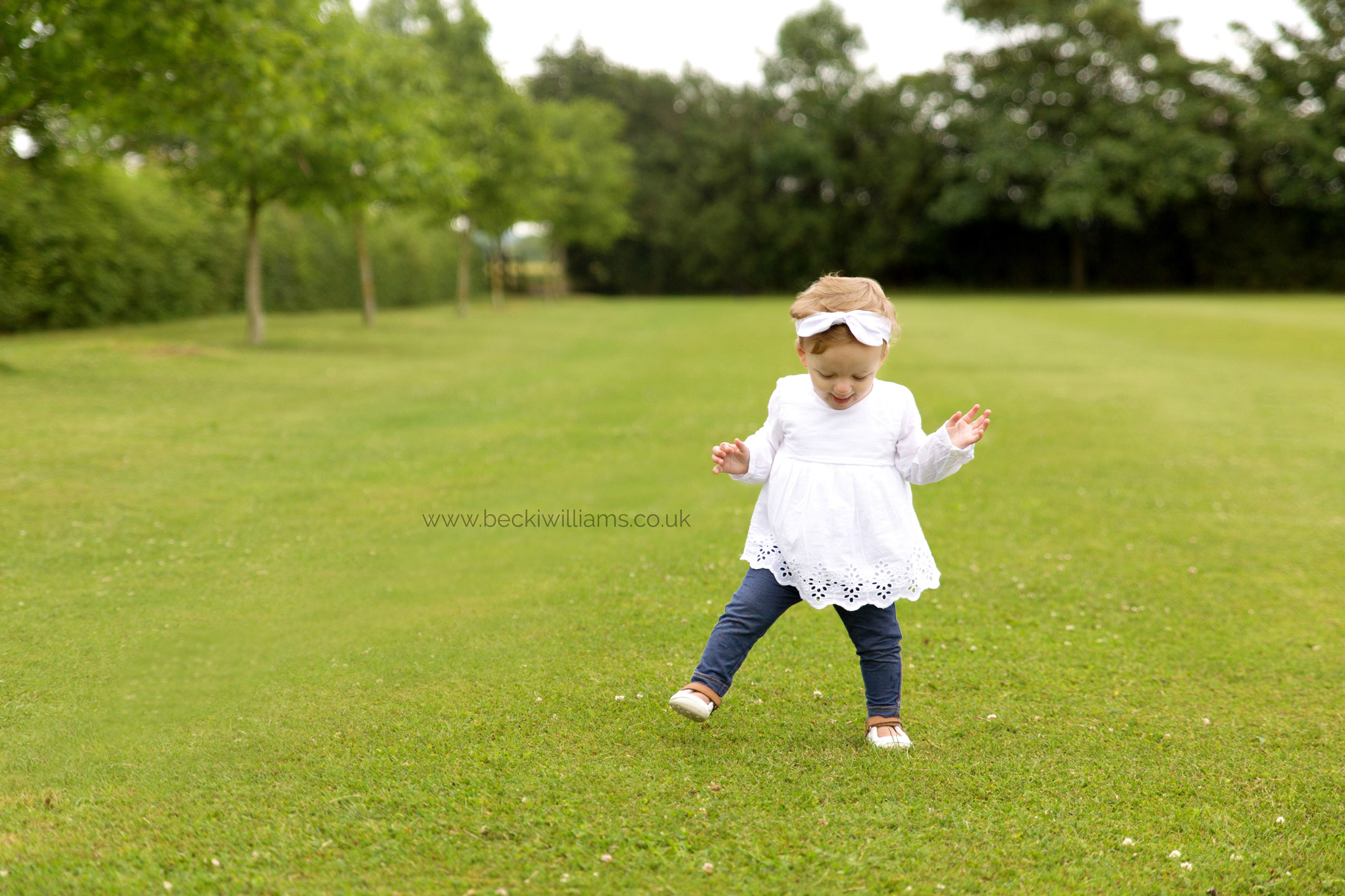 1 year old walking unsteadily in a park in hitchin