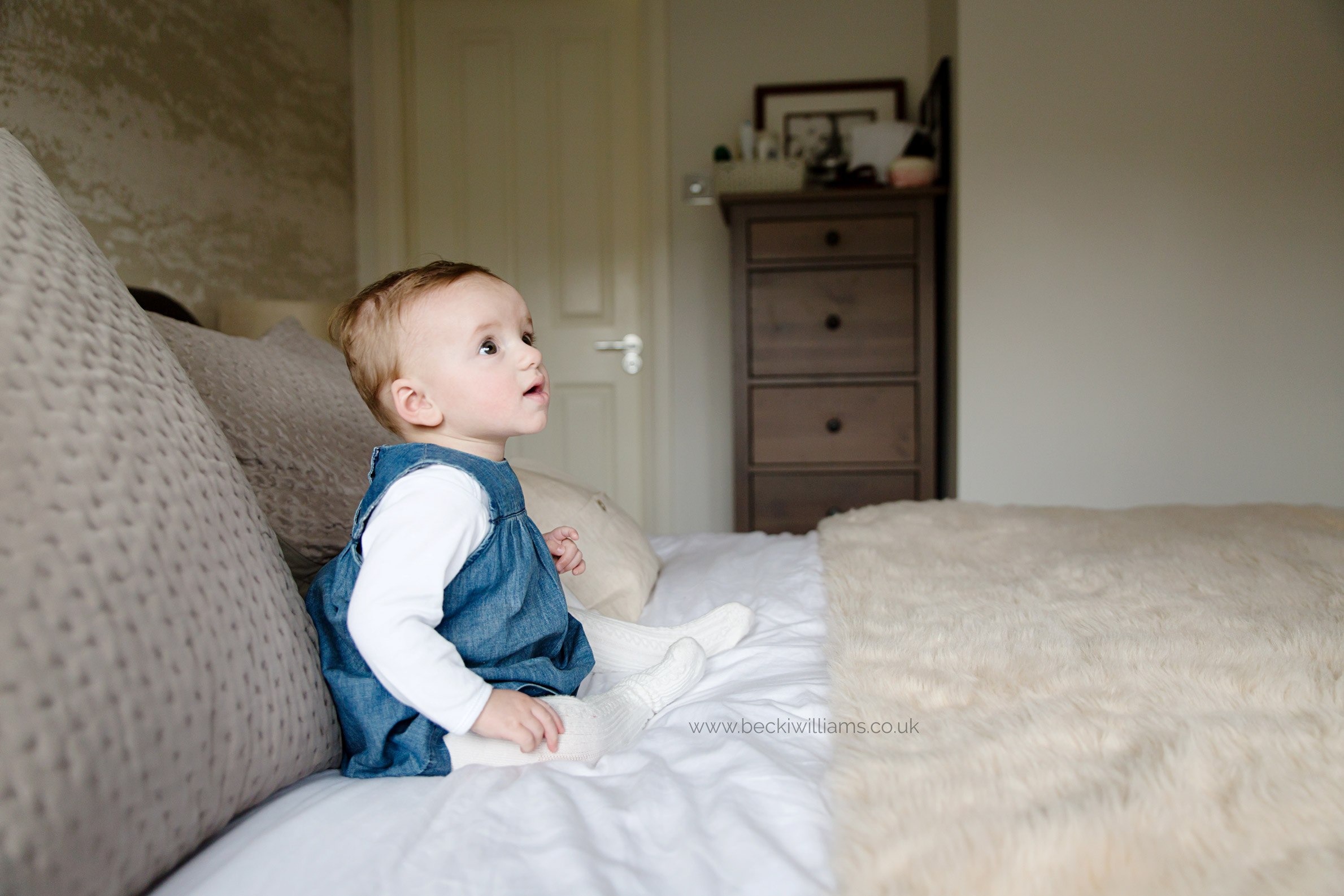 8 month old girl sits on bed for professional photography in hitchin