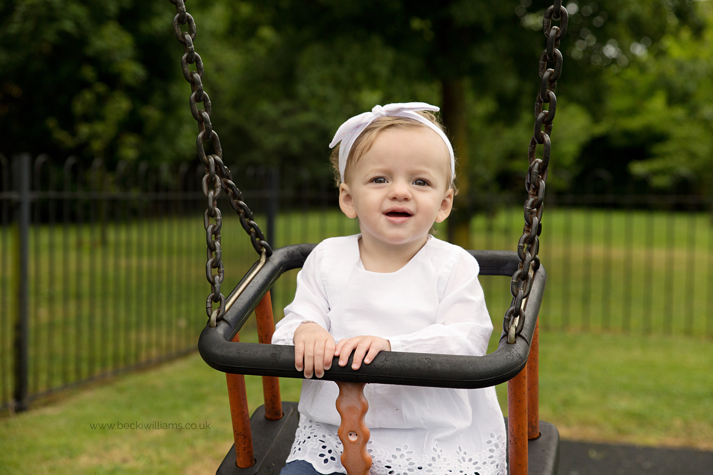 1 year old swings on swing with dad for professional photography