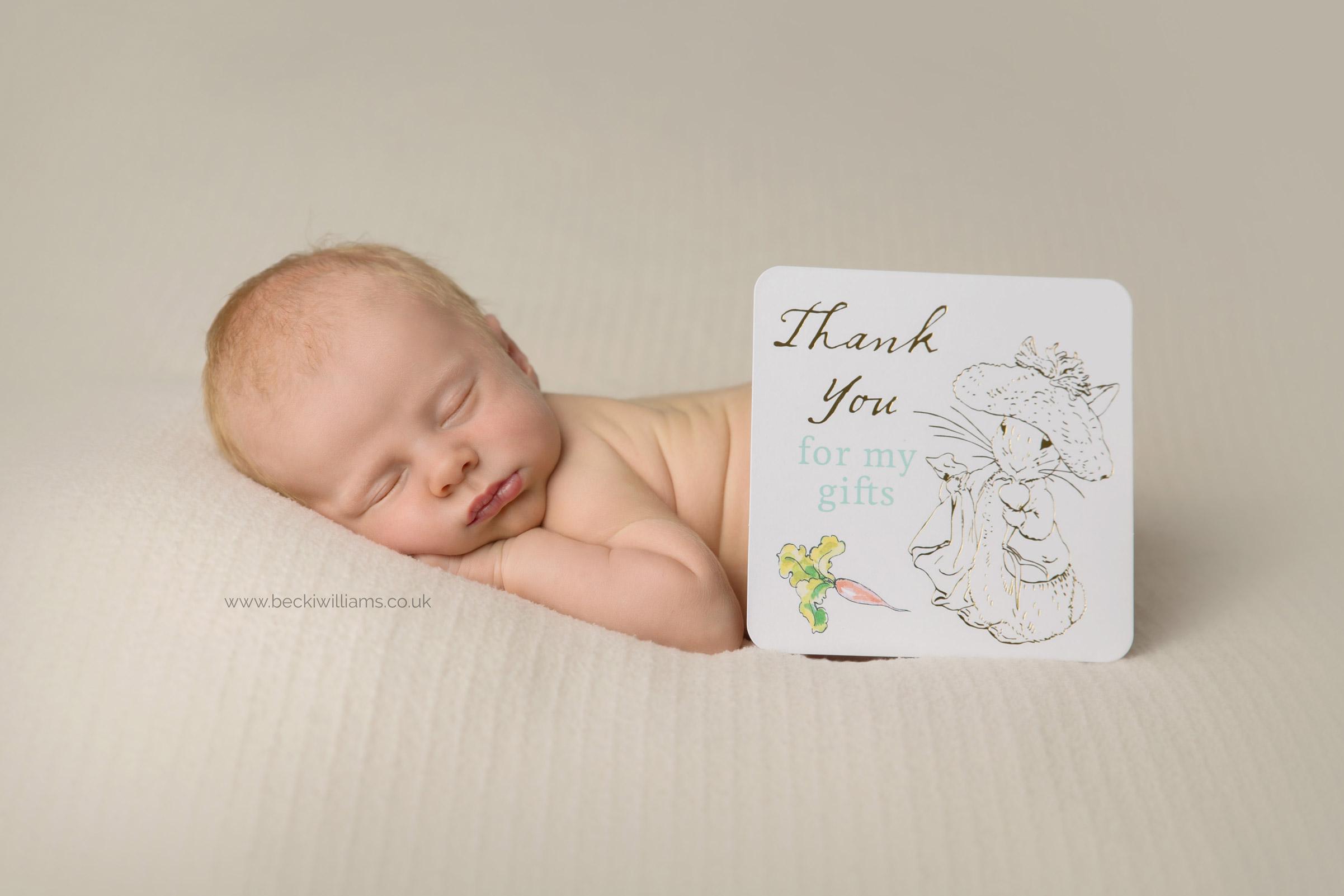 newborn boy sleeps on his tummy with a thank you card