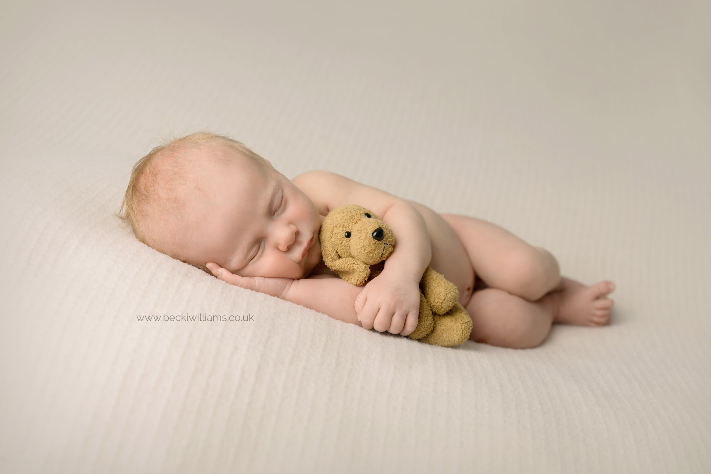 newborn boy cuddles toy dog while asleep