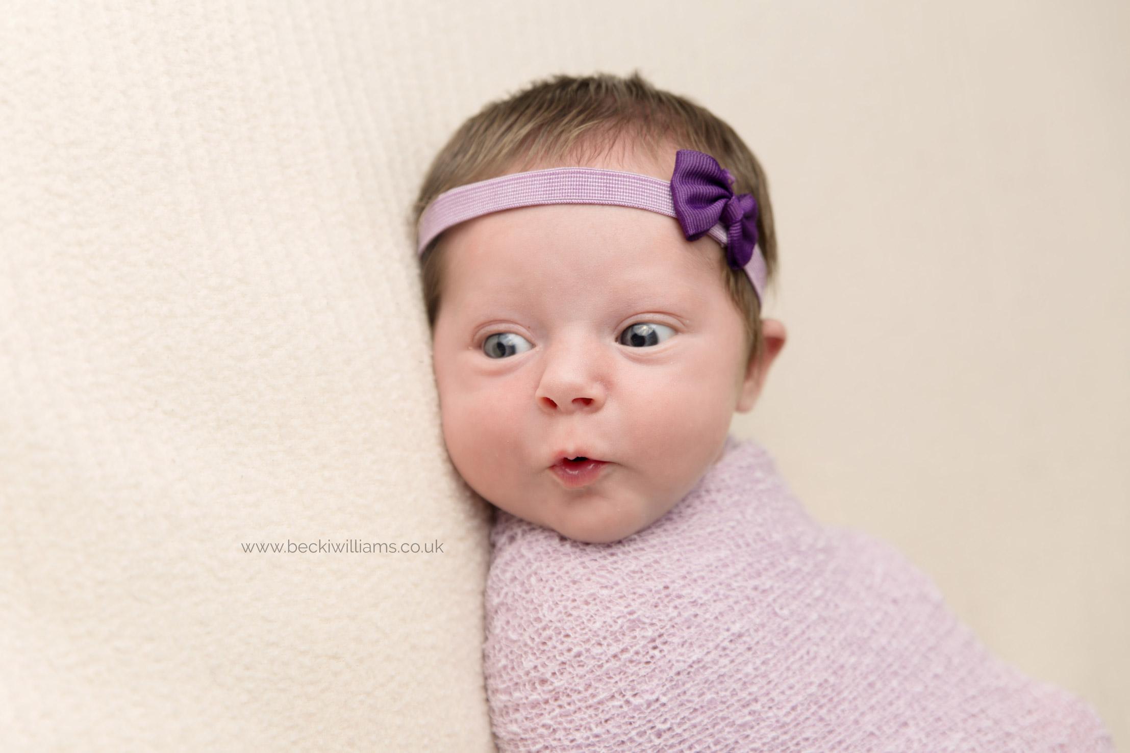 Newborn pulls funny face during her newborn baby photo shoot in Hemel Hempstead