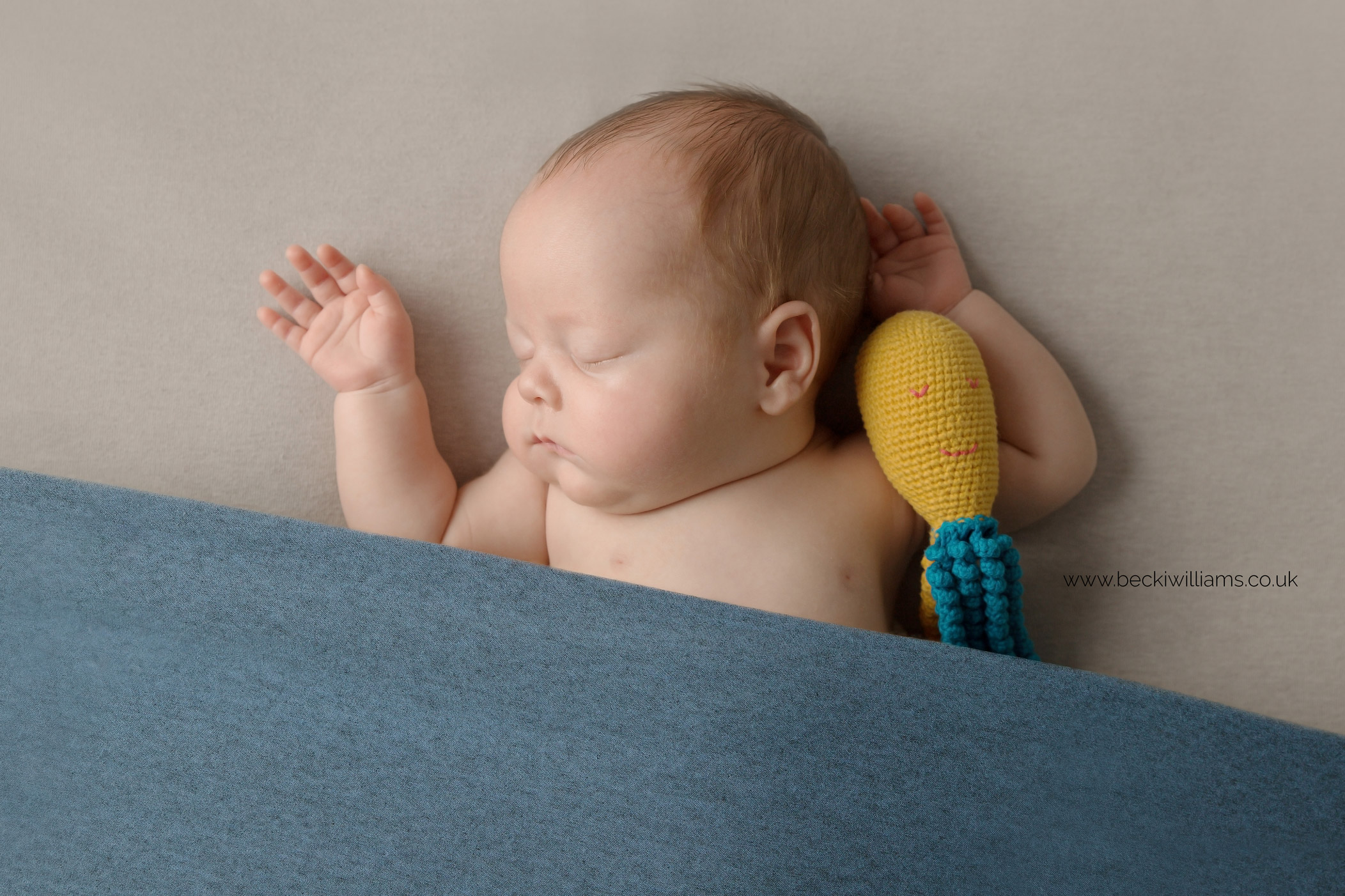 newborn boy hugging his octopus for a preemie toy for newborn baby photo shoot in hemel hempstead