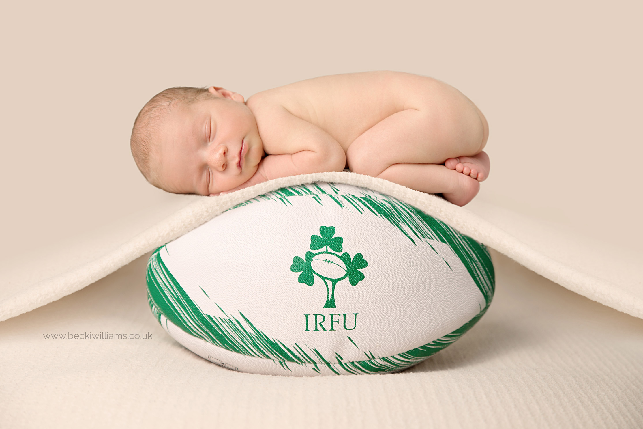 newborn baby on rugby ball for newborn baby photoshoot in hemel hempstead with becki williams photography - this is a composite!