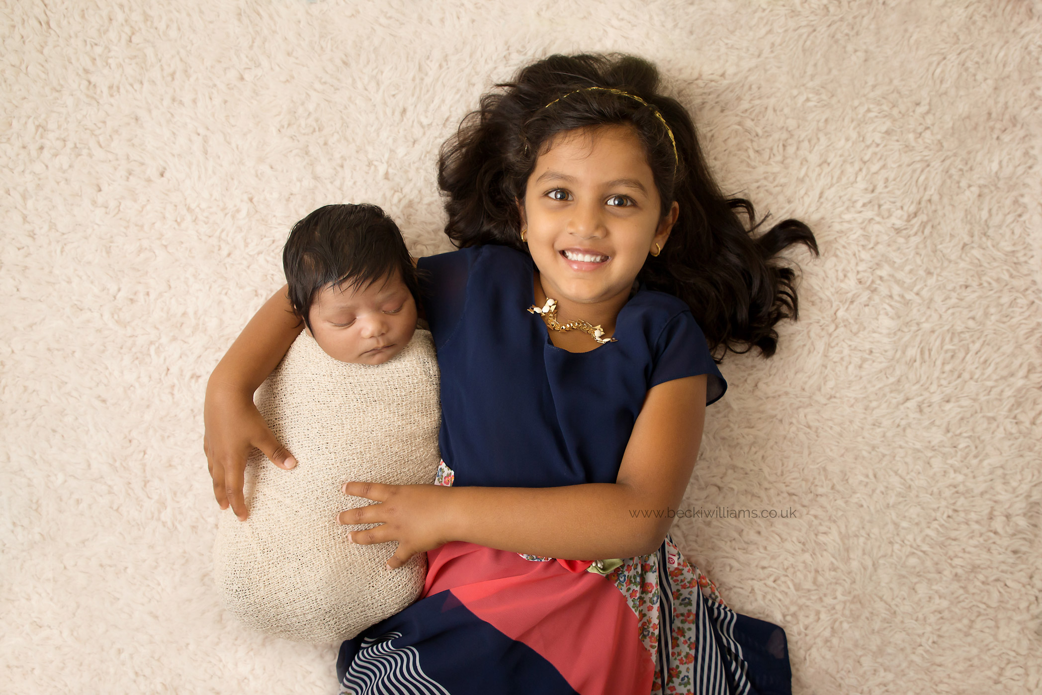 newborn baby laying in her big sisters arms on a cream blanket at their photo shoot in hertfordshire