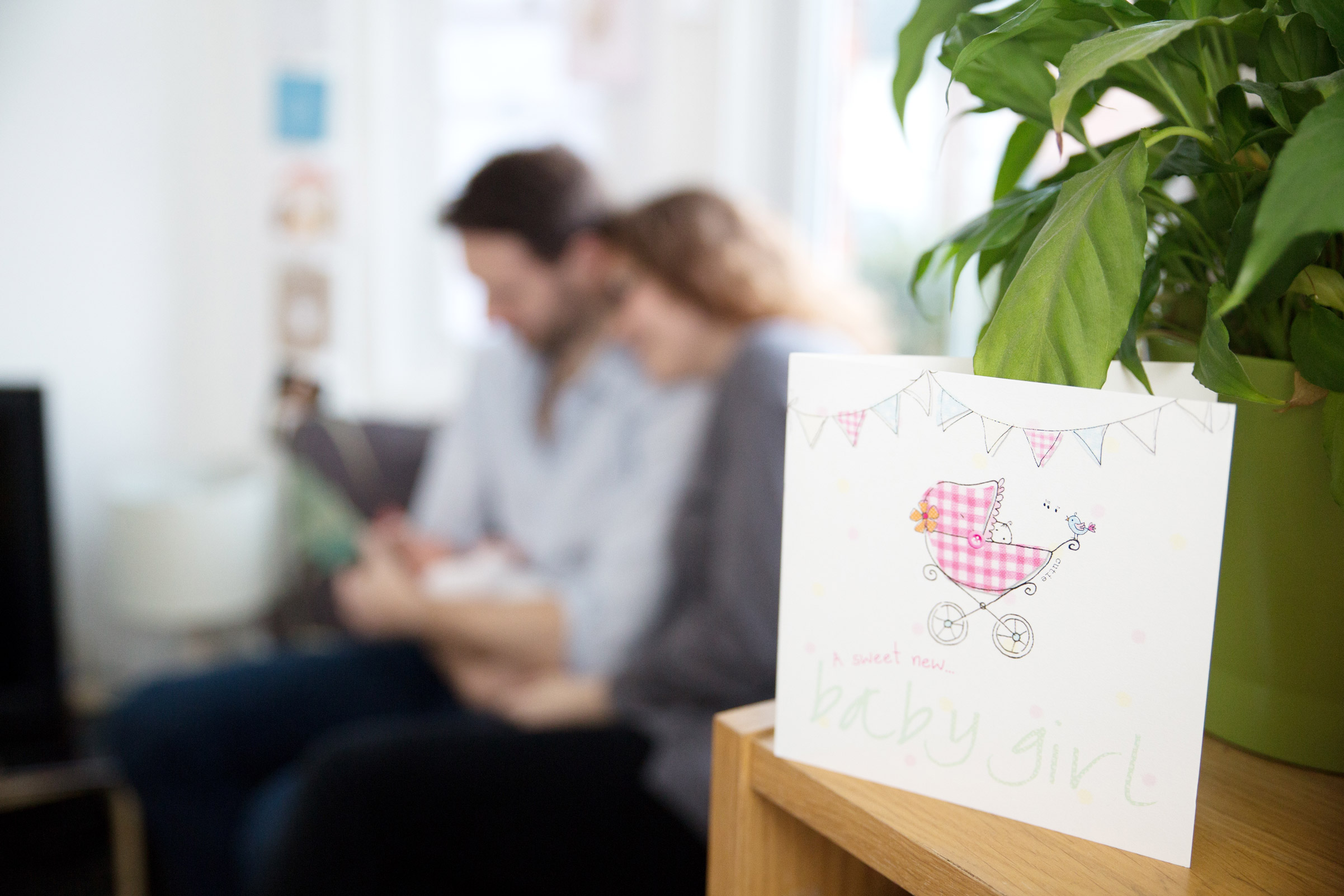 a card reading 'a sweet new baby girl with parents and baby out of focus in the background