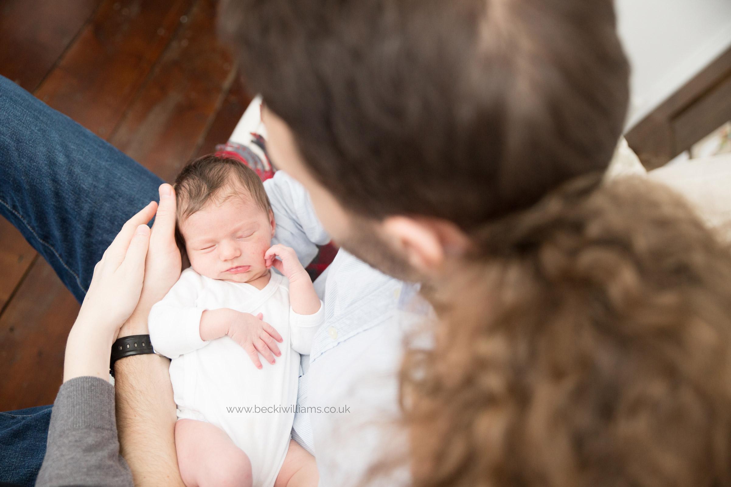 newb parents hold their newborn baby girl