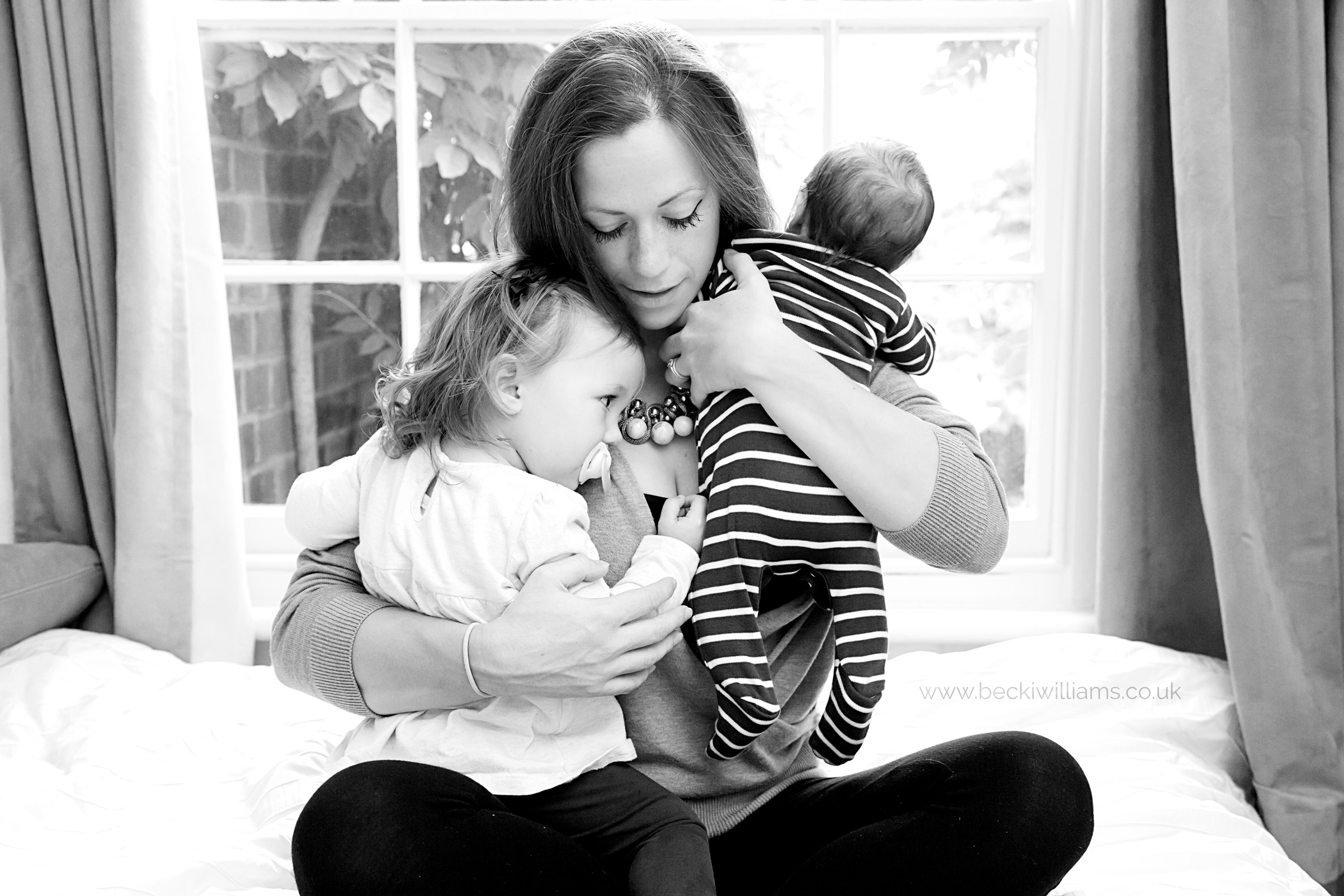 mum holds her newborn boy and 1 year old girl in a cuddle. black and white