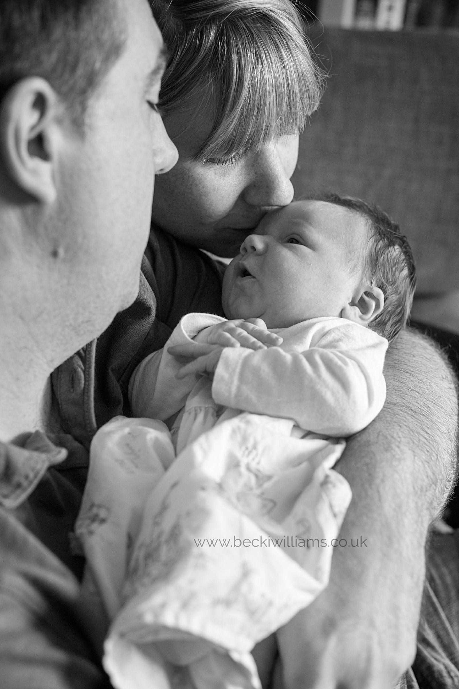 black and white photo of parents holding their newborn baby girl