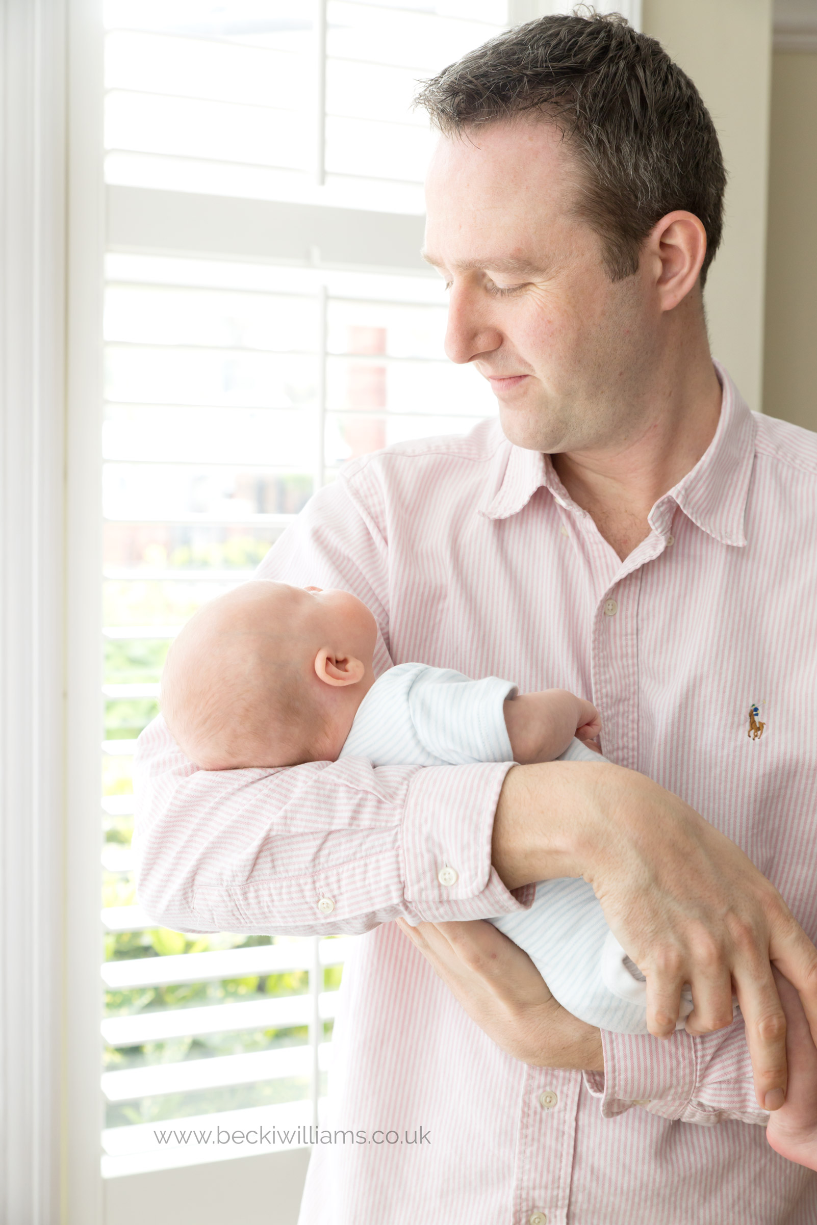 dad standing in beautiful window light holding his newborn baby son