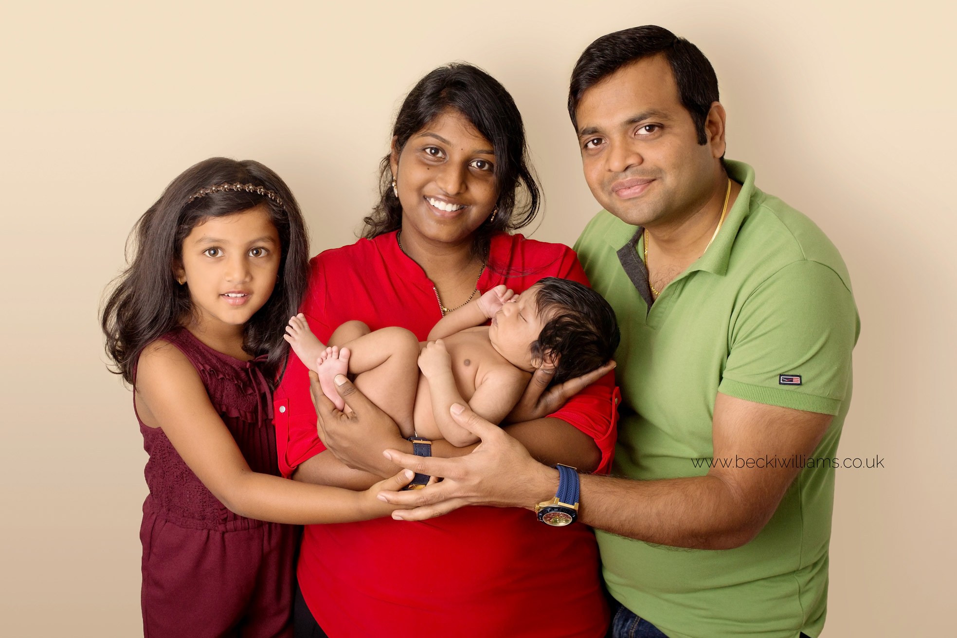 newborn baby being held by her mum with her dad and big sister for their newborn photo shoot in hemel hempstead