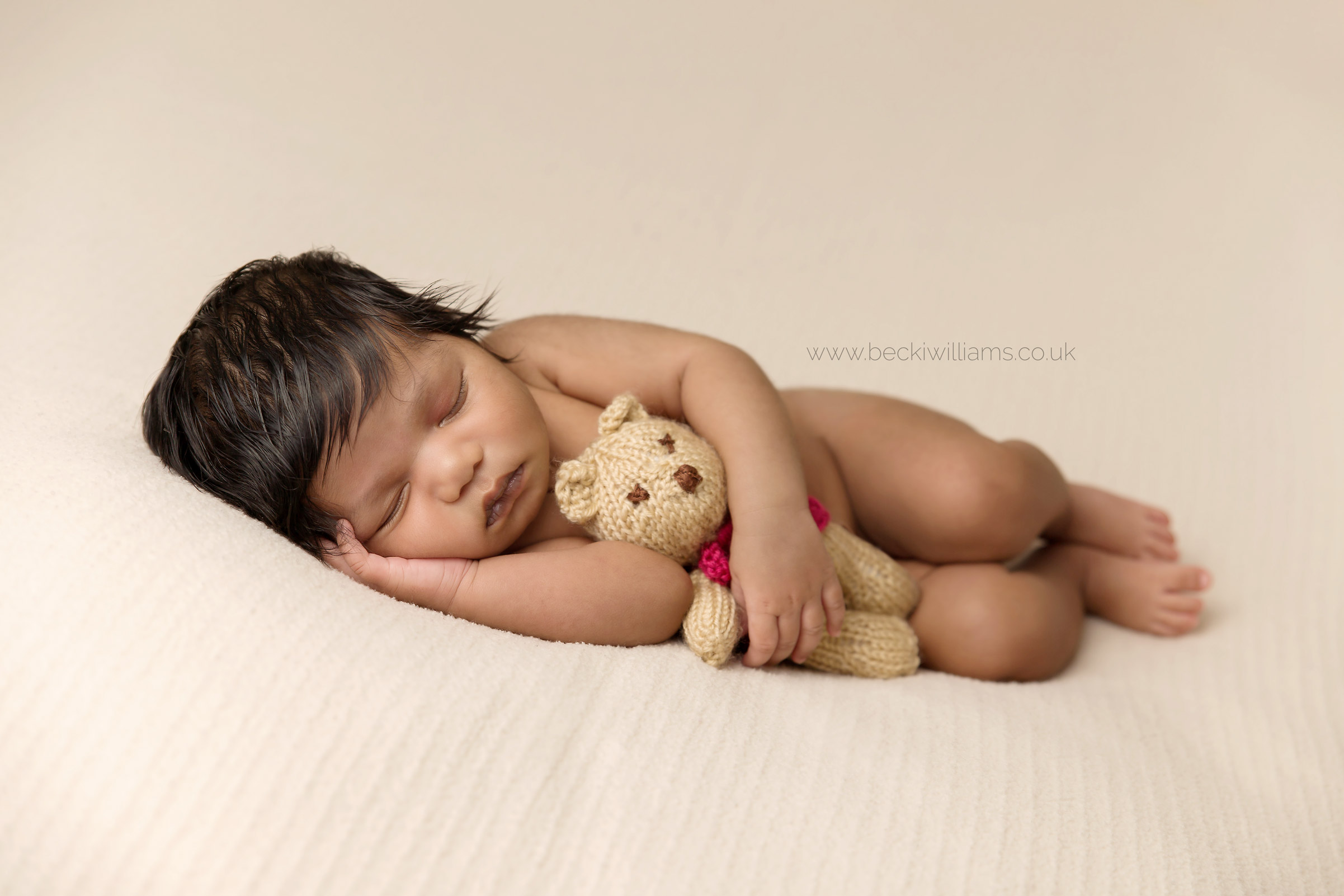 newborn baby girl laying on her side cuddling a toy bear for her newborn baby photo shoot in hemel hempstead
