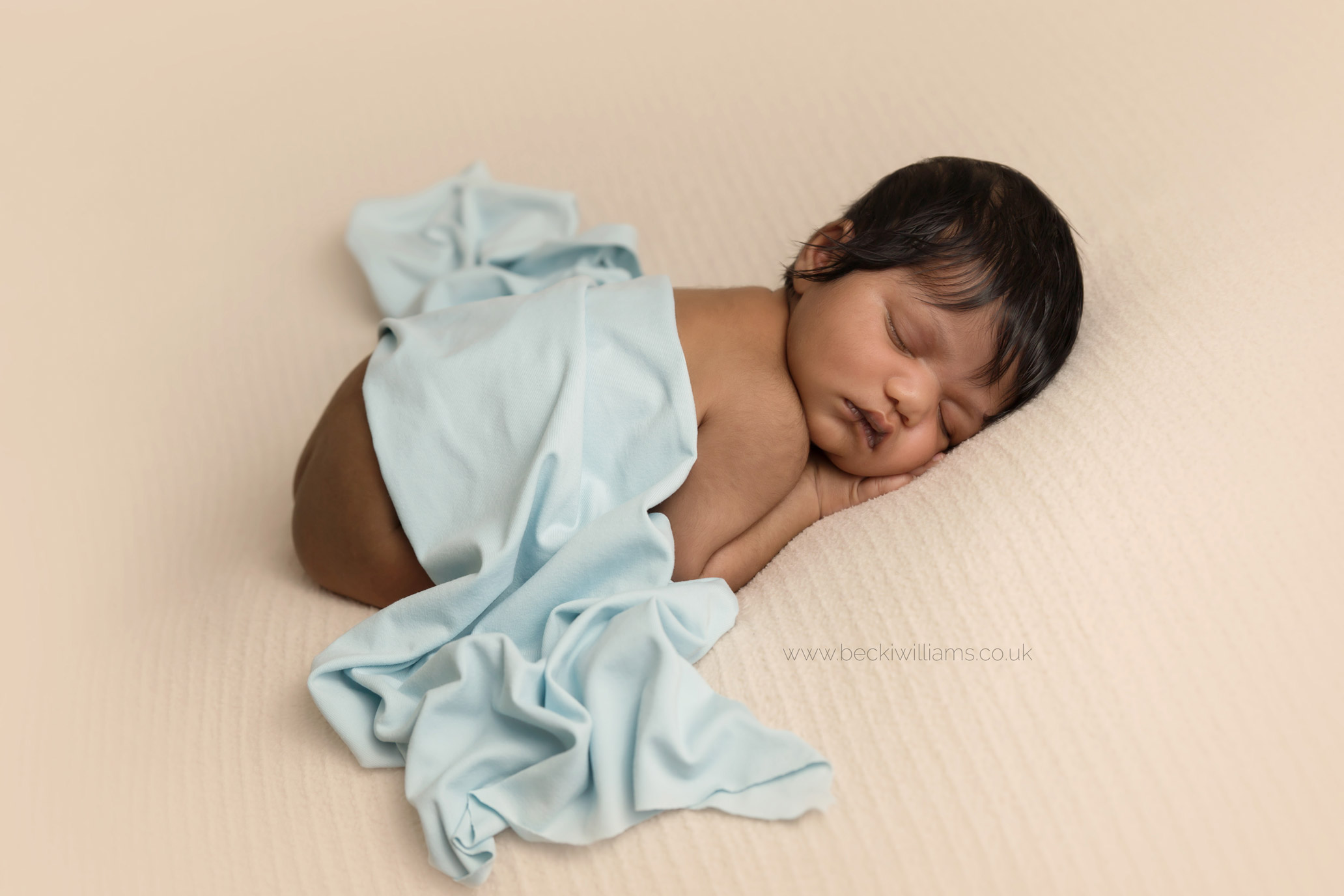 newborn baby girl laying on her tummy for her newborn photo shoot in hemel hempstead with a blue blanket