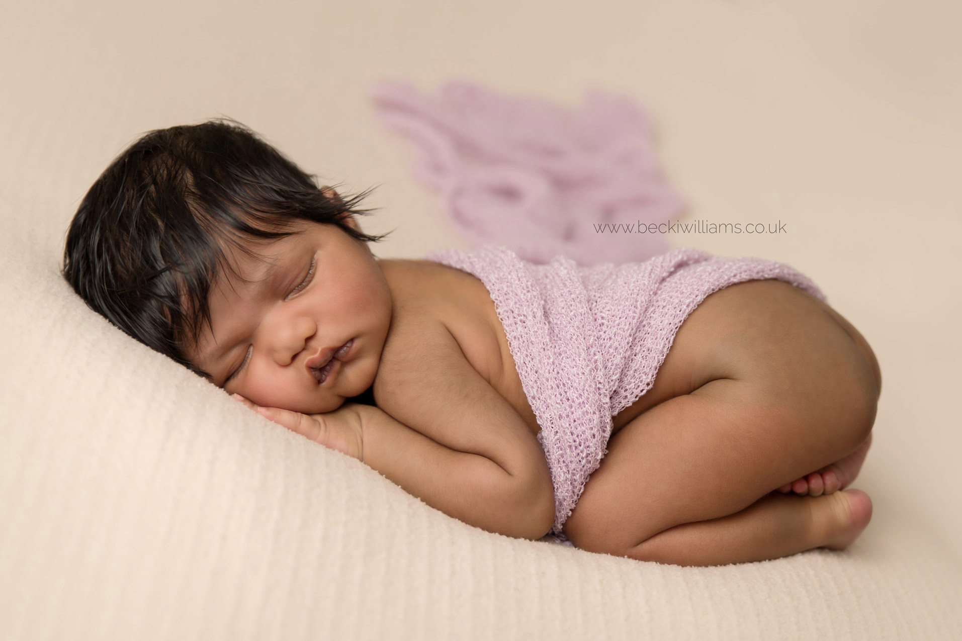 newborn baby girl laying on her tummy for her newborn photo shoot in hemel hempstead with a pink blanket