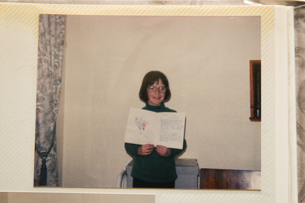 young girl in the early 90s holding a school book proudly