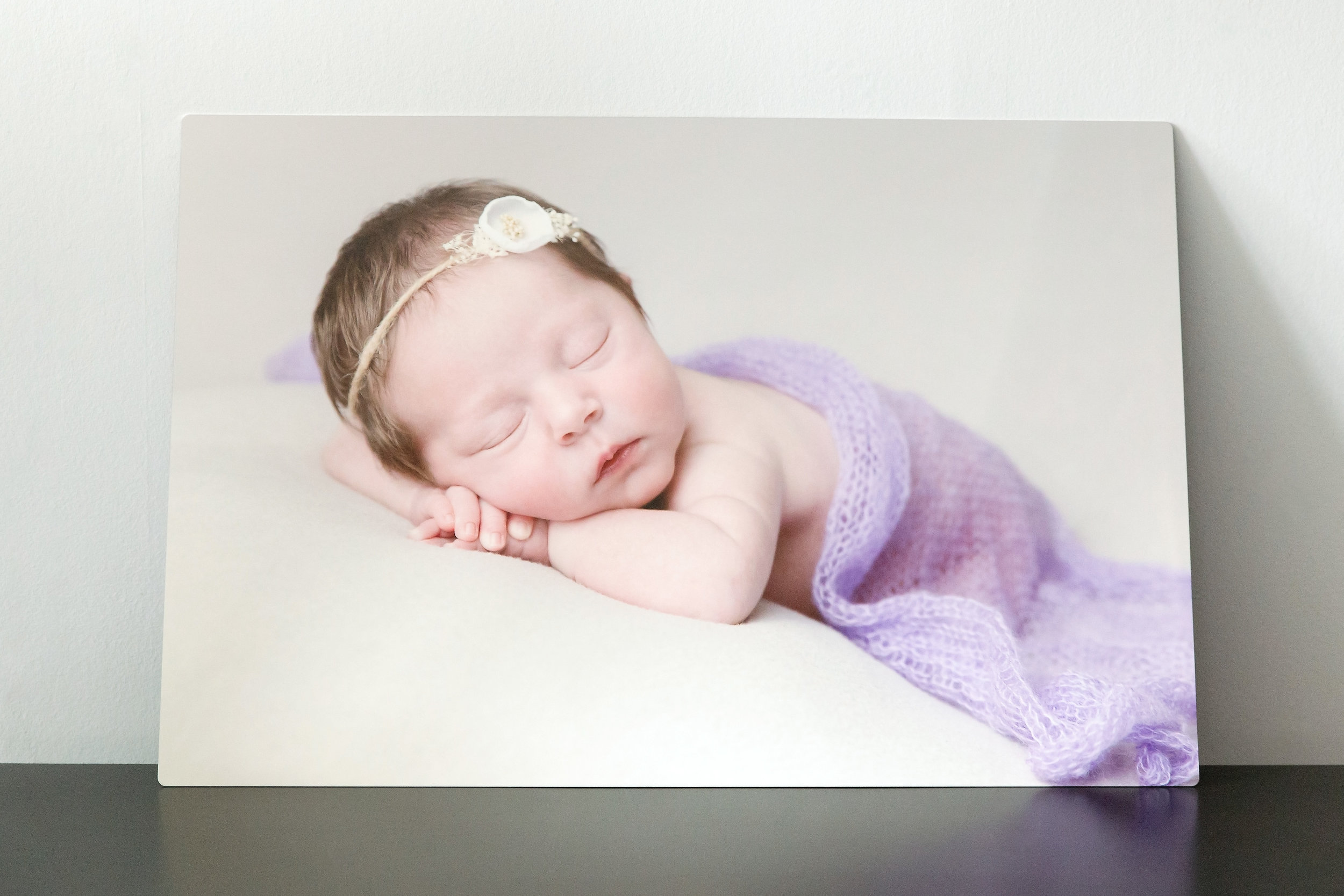 metal wall hanging of sleeping newborn girl covered in a thin purple blanket while wearing a white headband