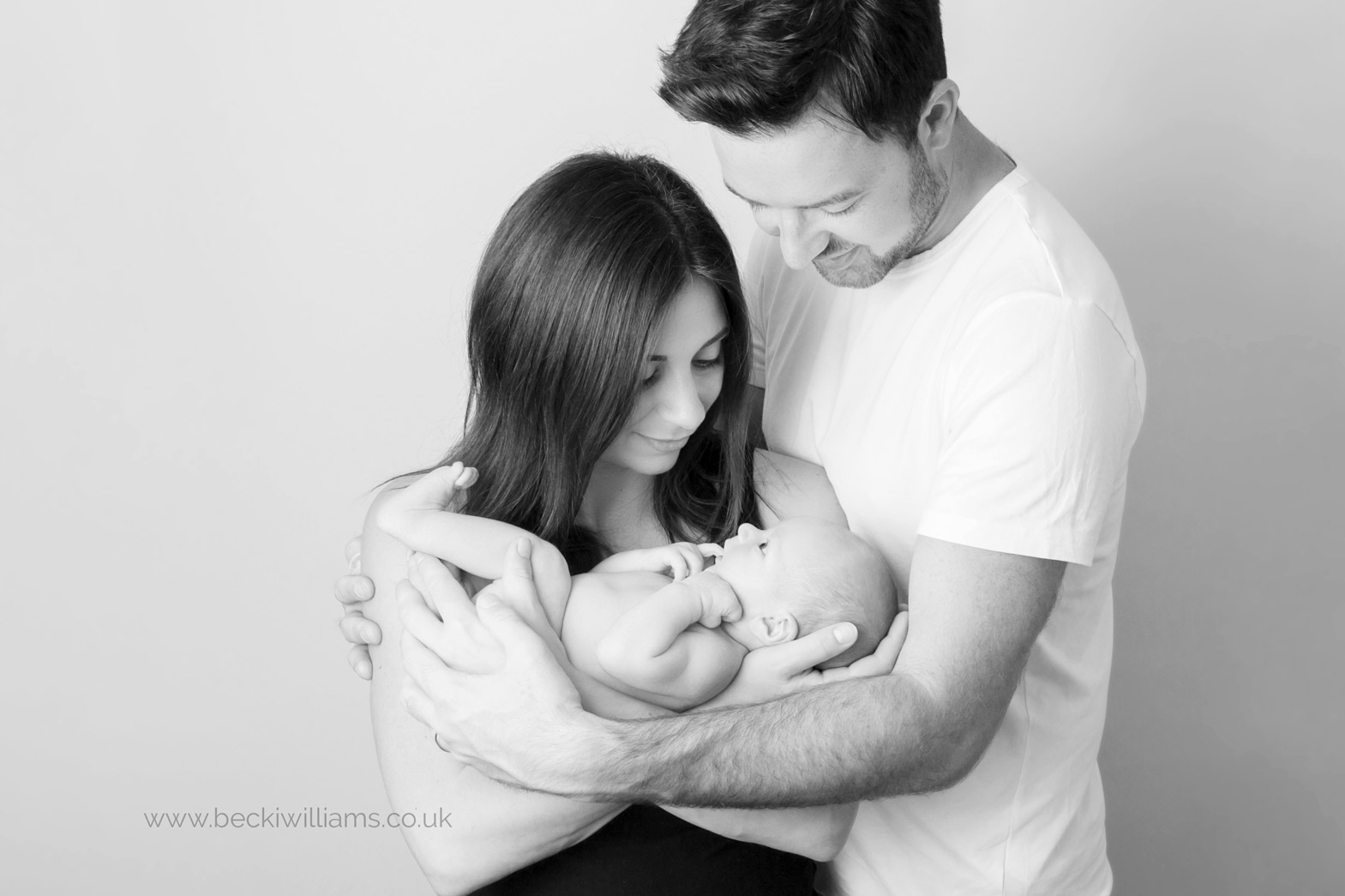 Mum and dad hold newborn baby in black and white