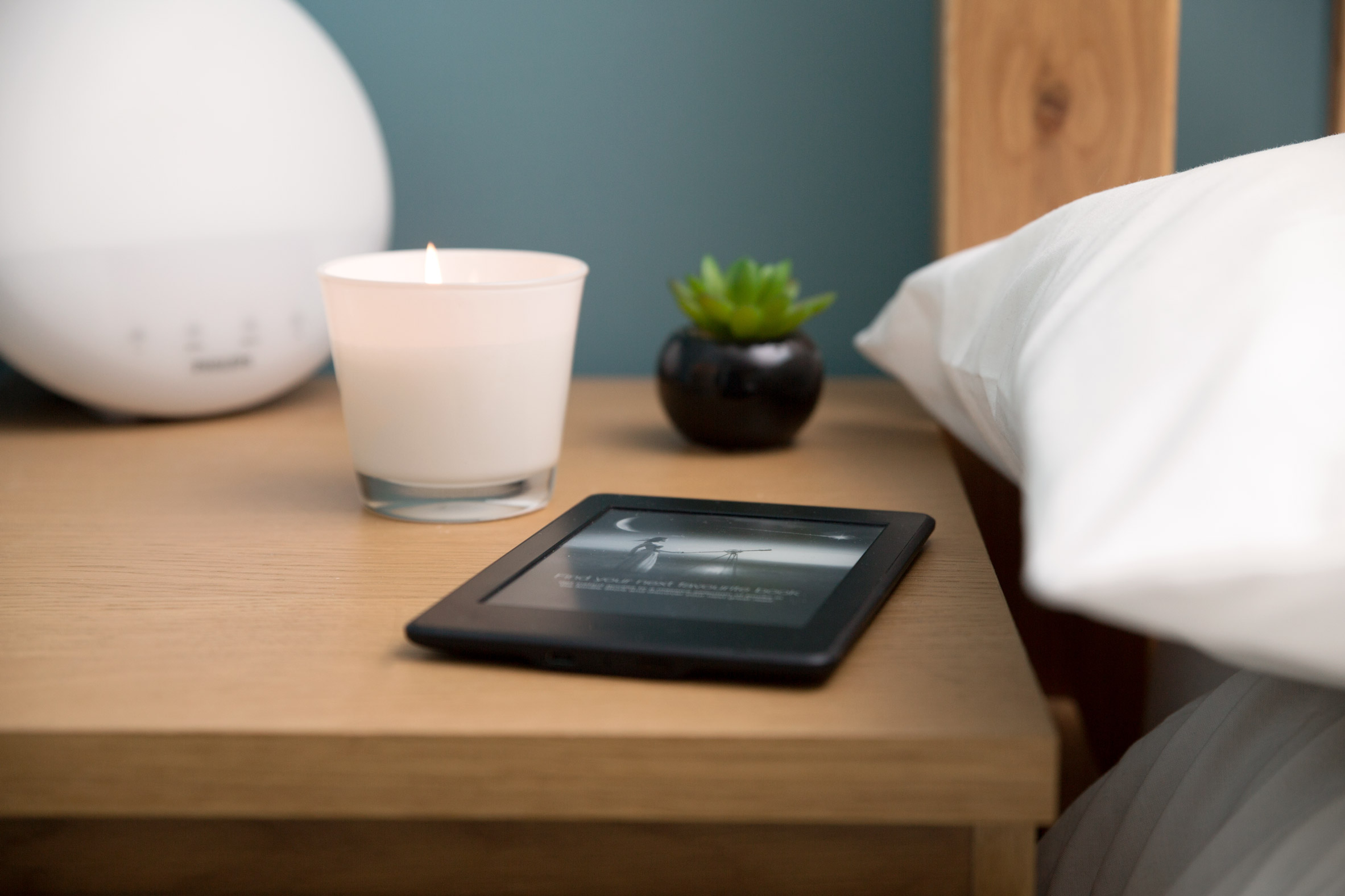 Kindle sits on a bed side table with a candle and a plant