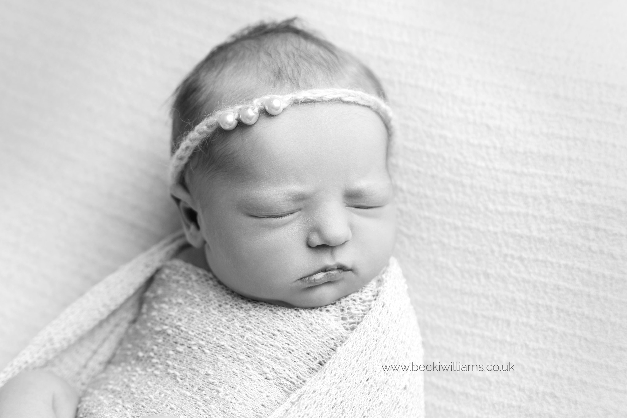 wrapped, sleeping newborn baby in black and white