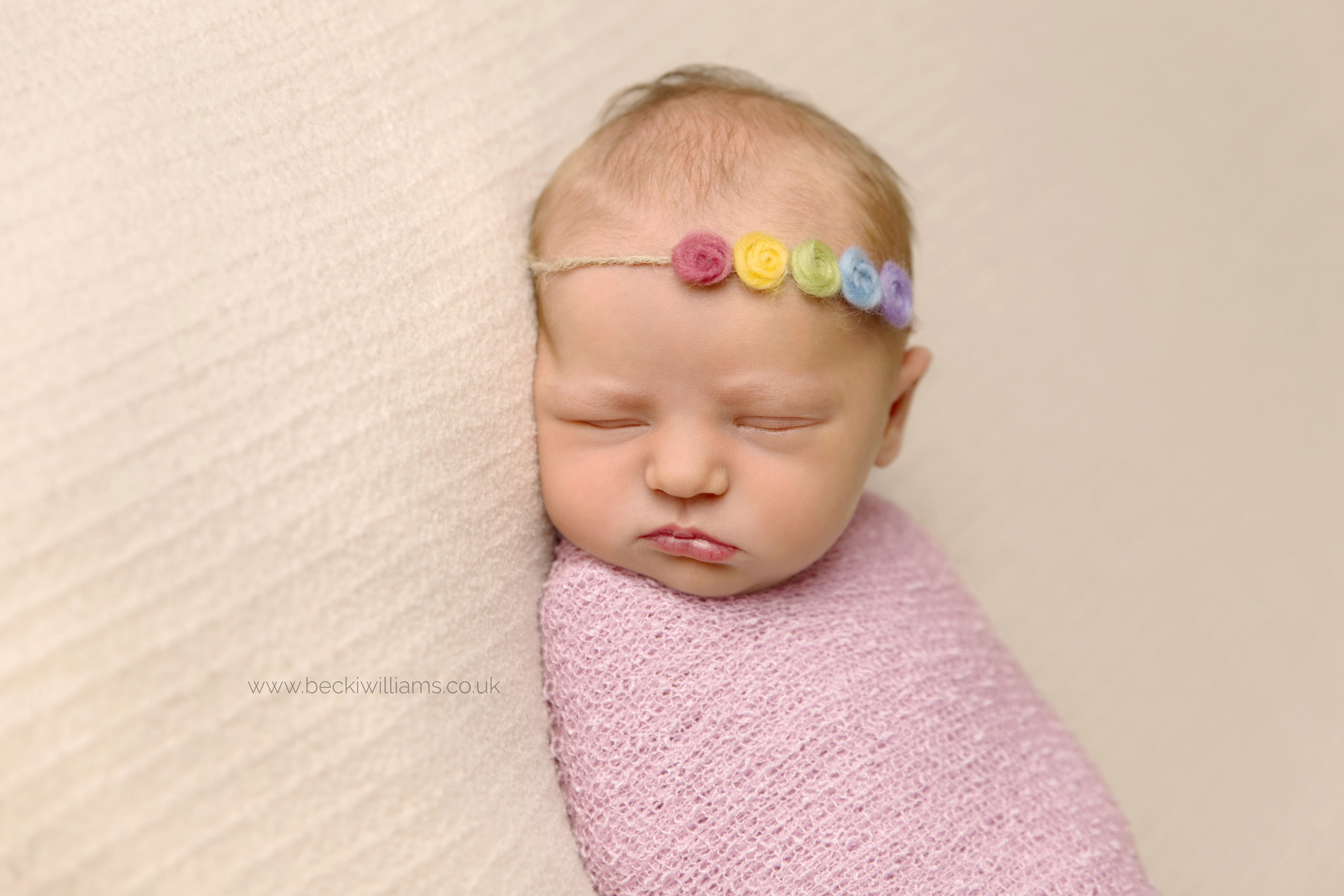 sleeping newborn baby wrapped in a pink blanket with a rainbow coloured headband on