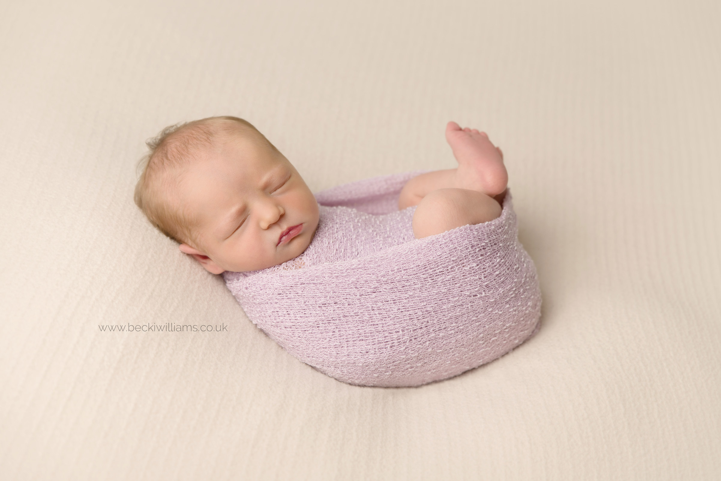 wrapped sleeping newborn baby with legs on show