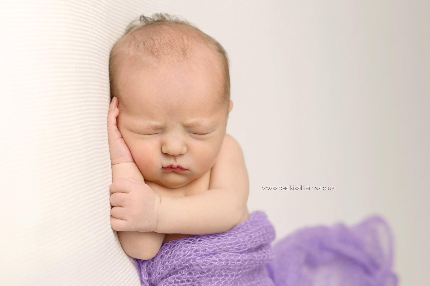 sleeping newborn baby covered in a purple blanket at her professional newborn photo shoot in hemel hempstead