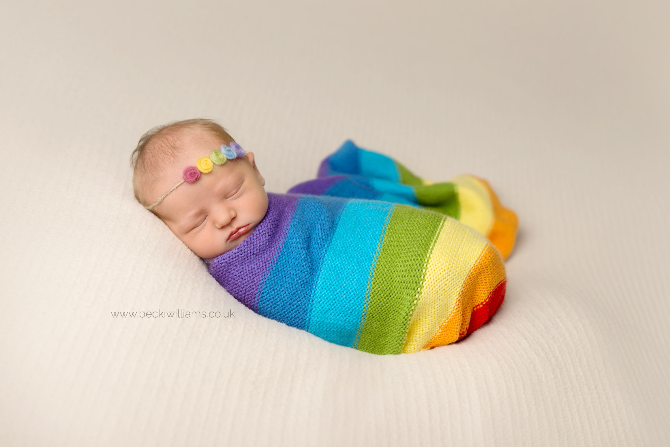 newborn baby wrapped in a striped, mulit-coloured blanket and wear a colourful headband