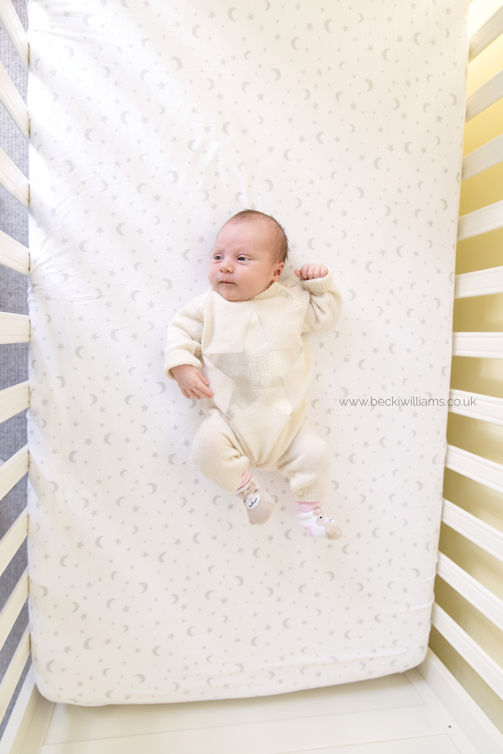 newborn baby girl looks tiny in her large white cot - becki williams photography
