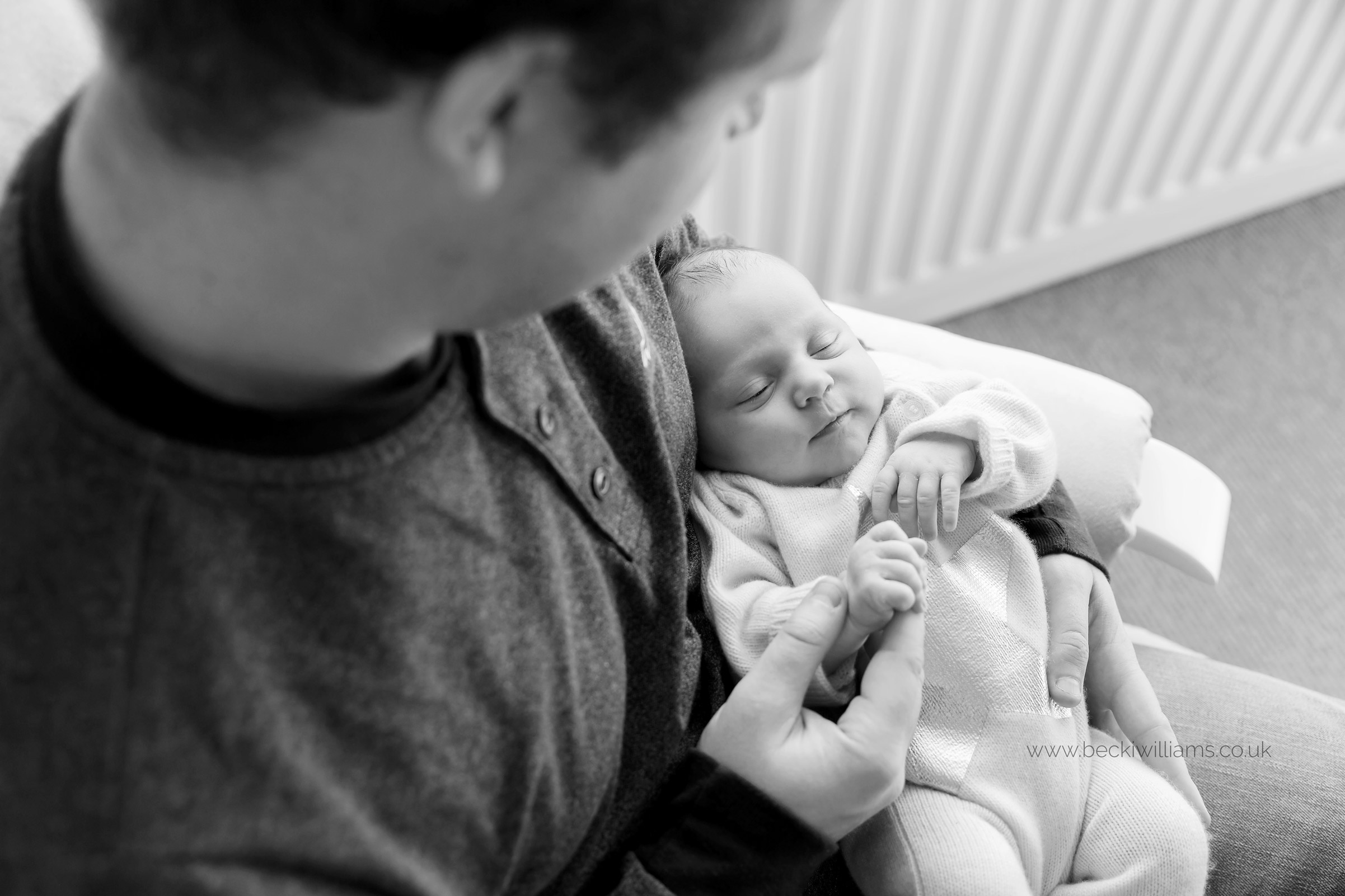 new dad sitting his newborn baby girl's neutral nursery on a rocking chair, holding his baby