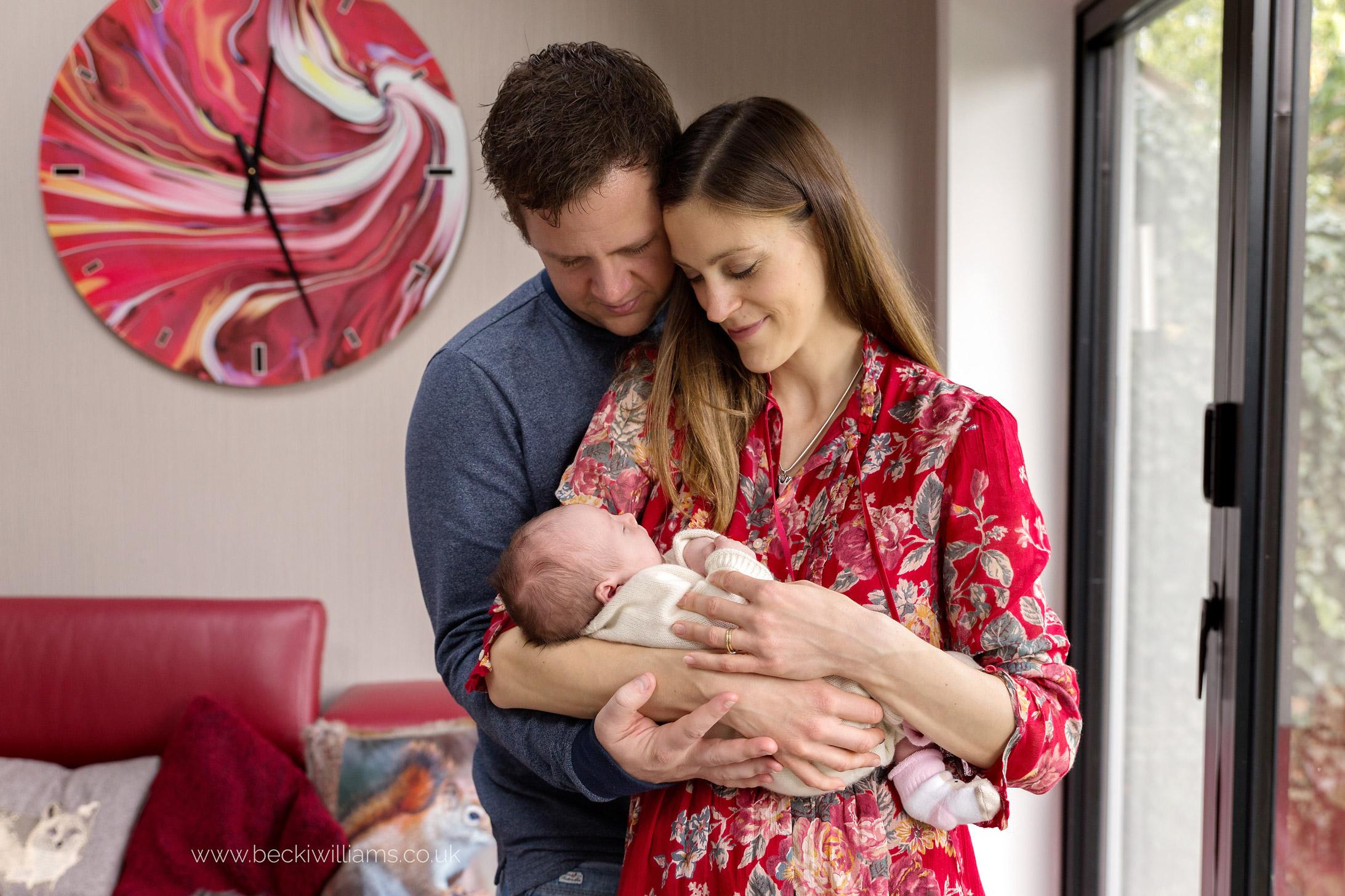 new parents holding their newborn baby, staring at her lovingly in redbourn, hertfordshire