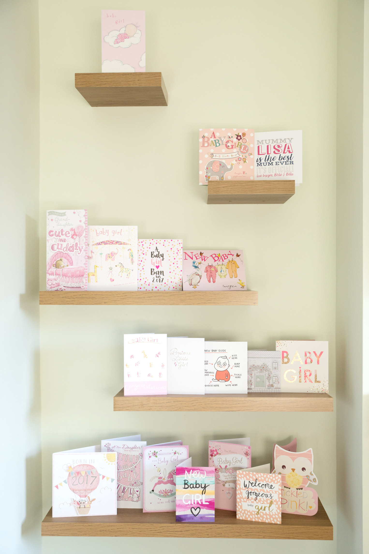 newborn baby cards sitting on shelves, welcoming a little girl in the world