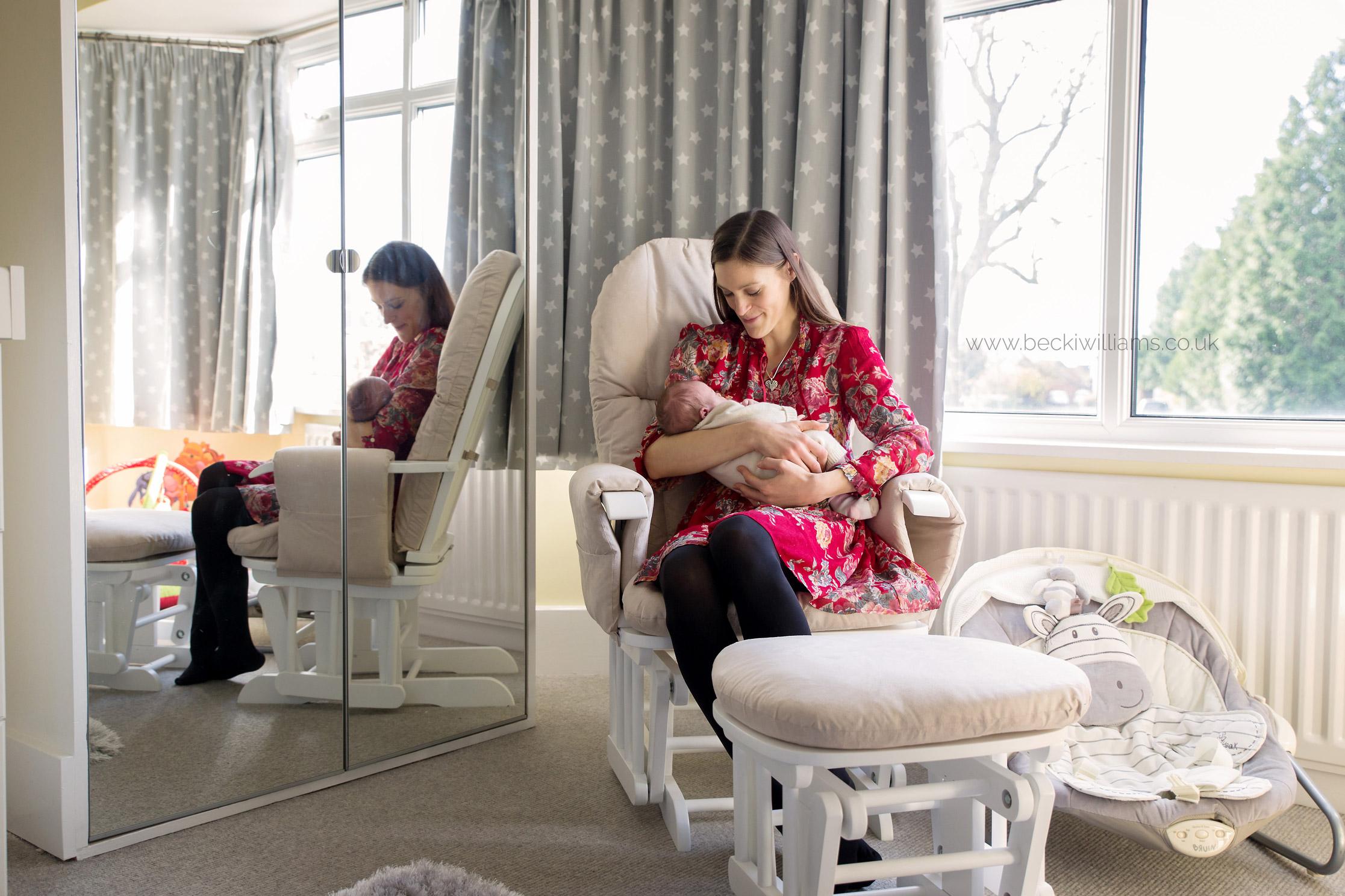 new mum sitting her newborn baby girl's neutral nursery on a rocking chair, holding her baby
