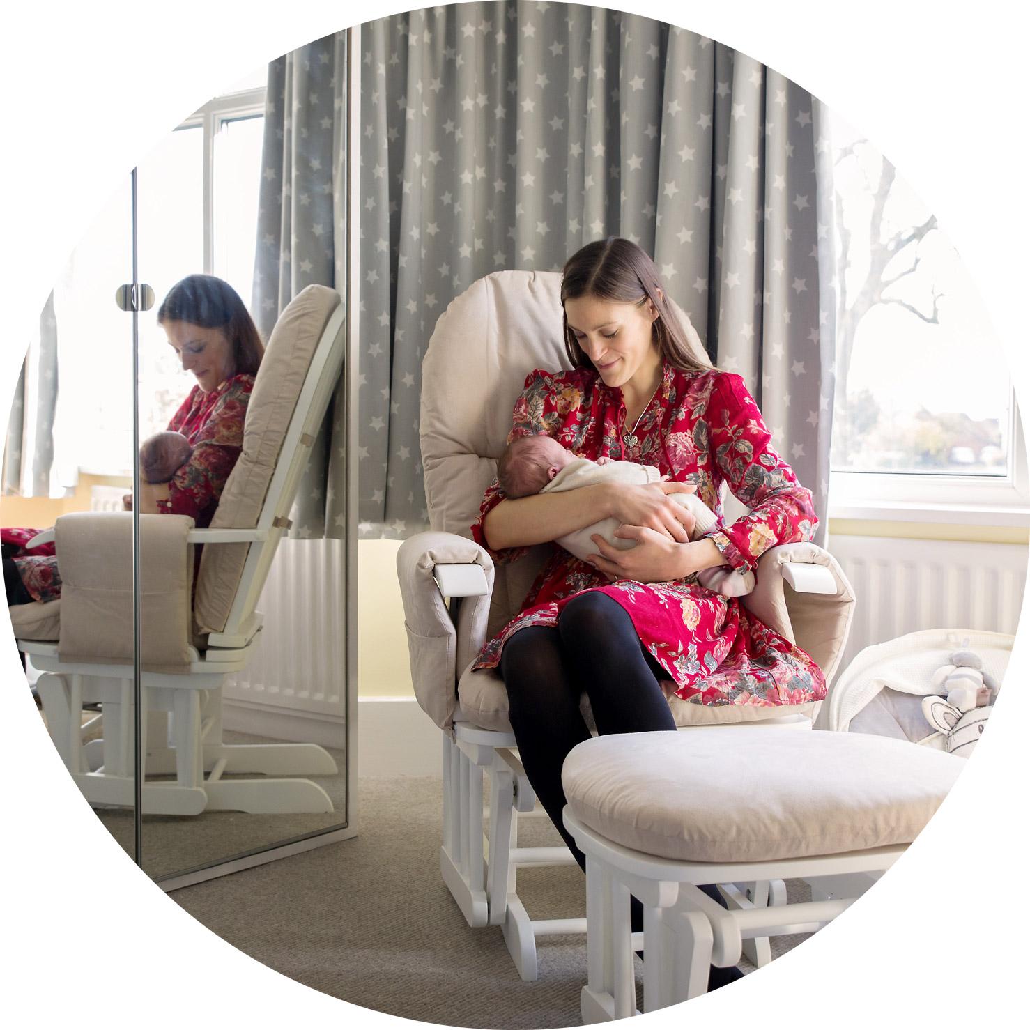 new mum sitting in her newborn baby girls nursery staring down lovingly at her little girl.