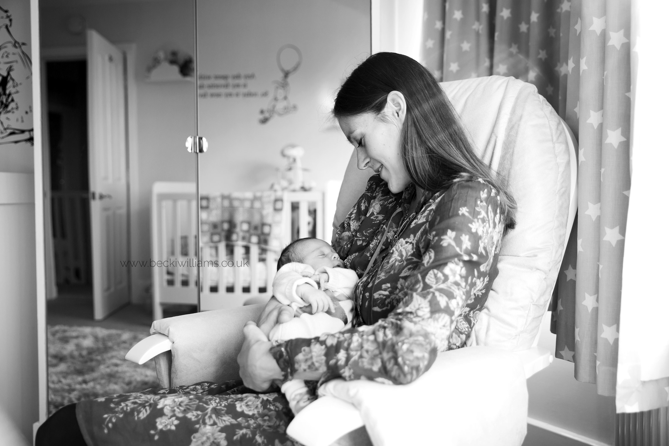 New mum sits in a rocking chair in a nursery holding her newborn baby girl.