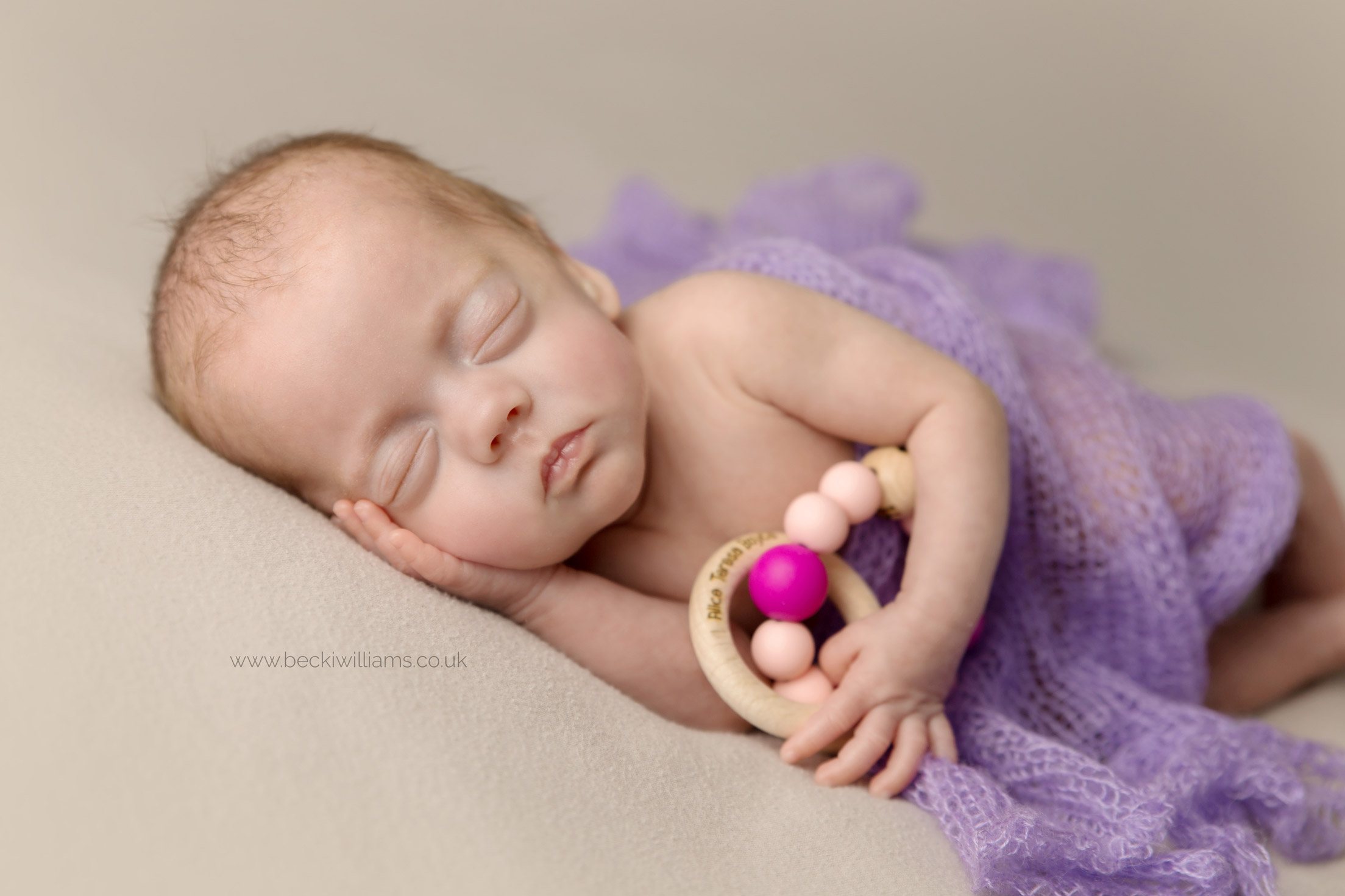 newborn baby girl lays asleep holding a wooden theether.