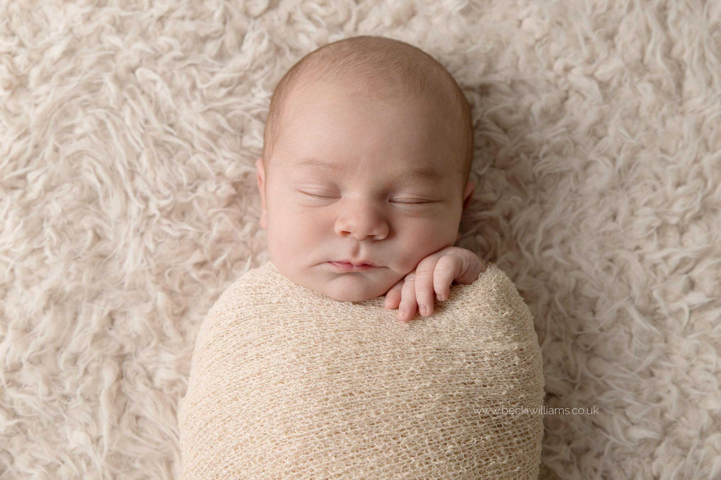 sleeping newborn baby boy wrapped in a cream blanket on a cream fluffy throw
