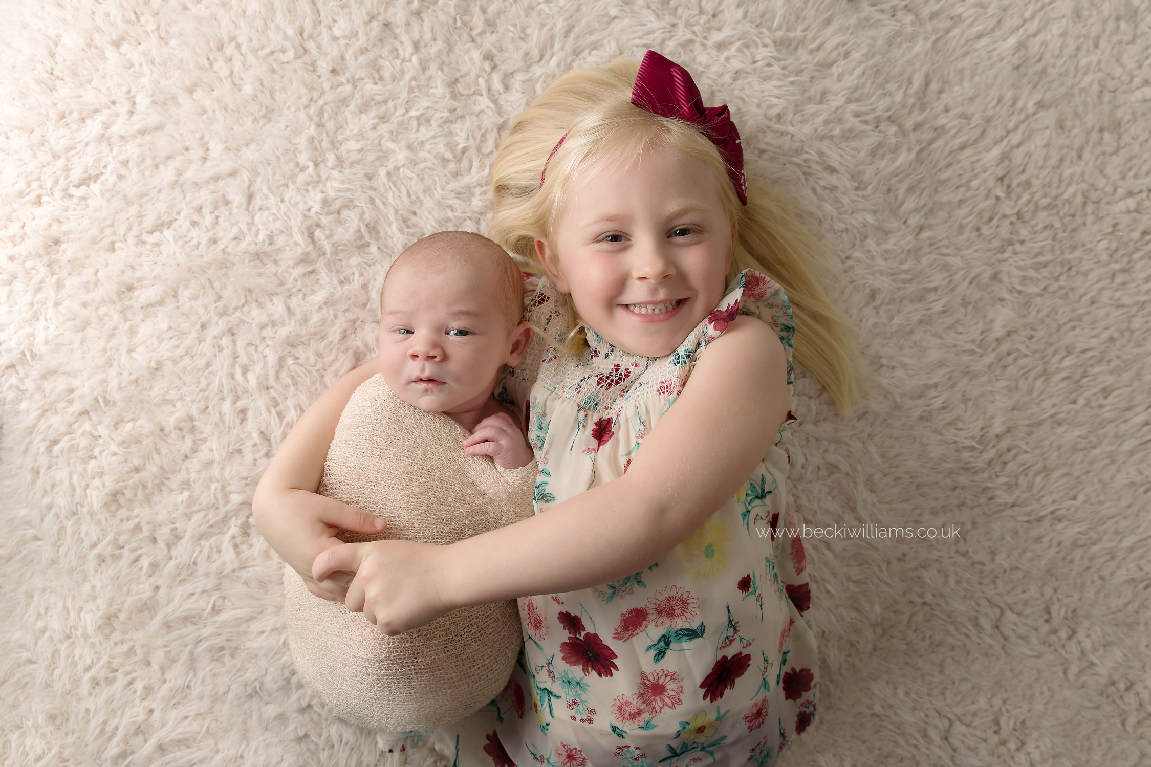 smiling big sister cuddles her newborn baby brother on a cream fluffy blanket