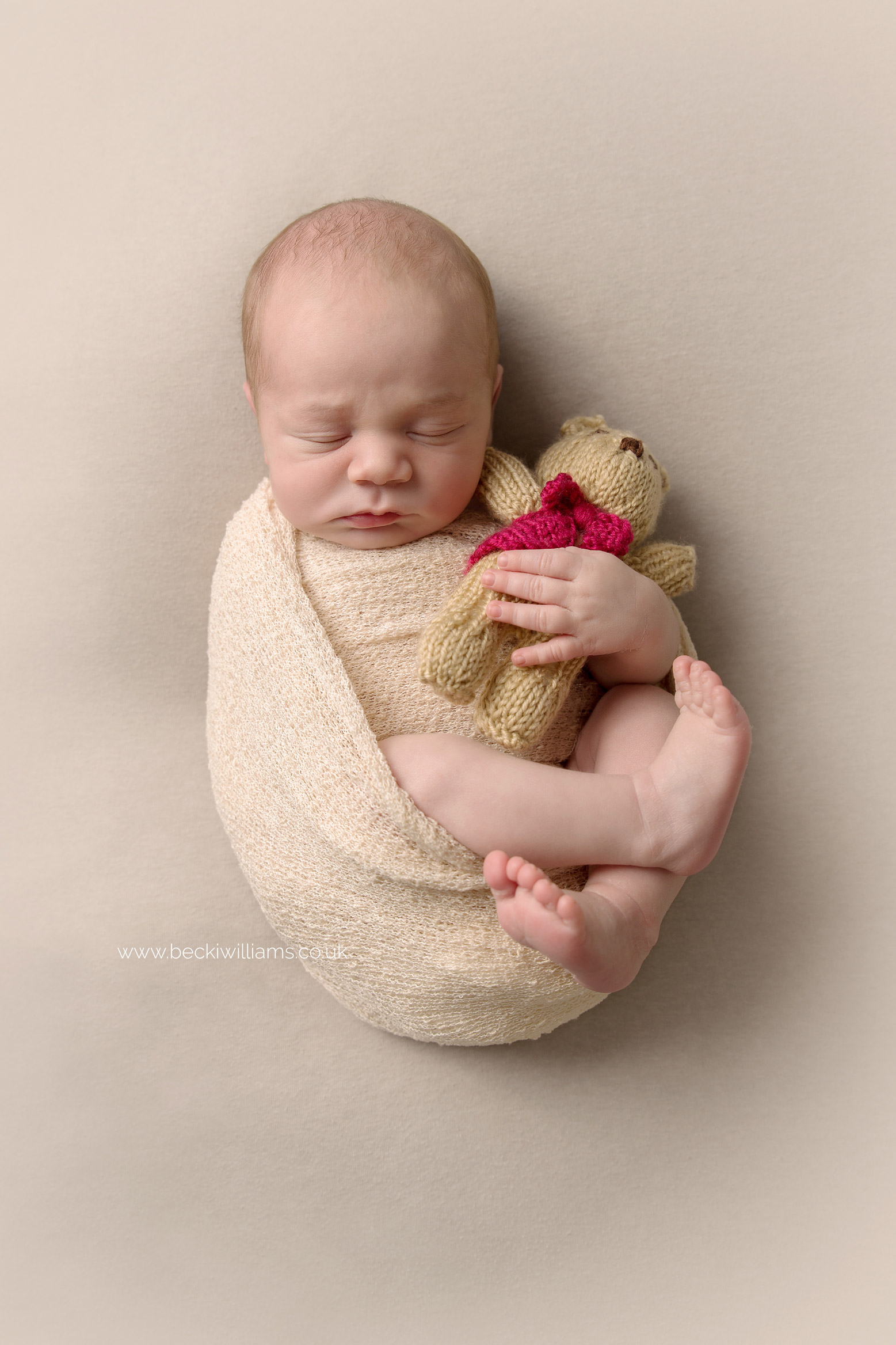 sleeping newborn baby boy wrapped in a cream blanket holding a little teddy dear