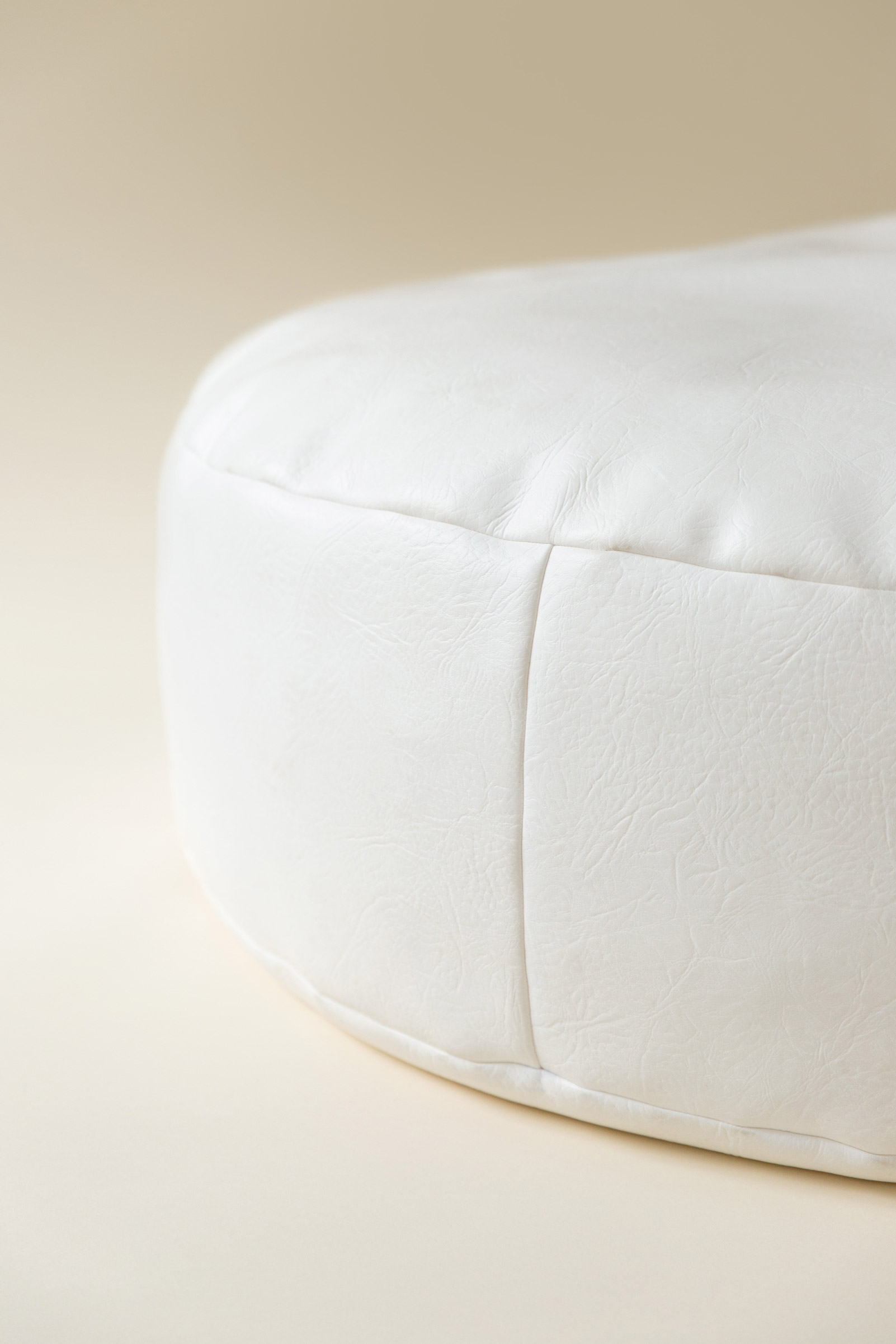 Newborn posing beanbag on a cream seamless paper backdrop