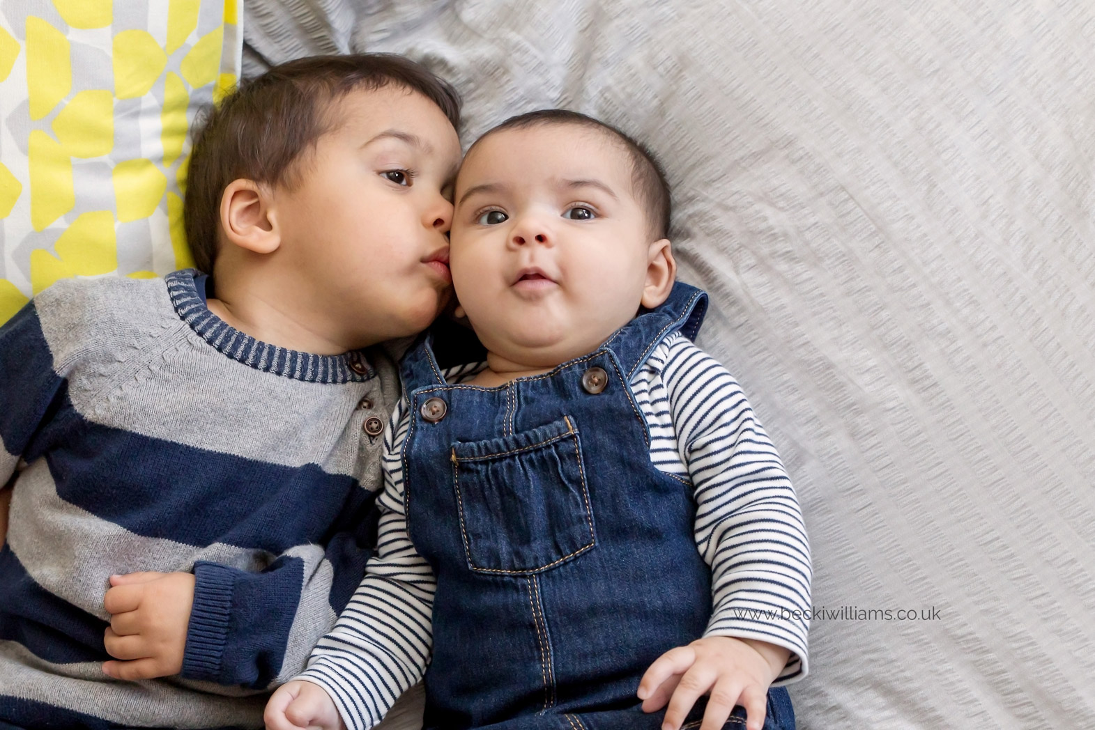 2 year old brother kisses his baby sister on the cheek while laying on his parents bed