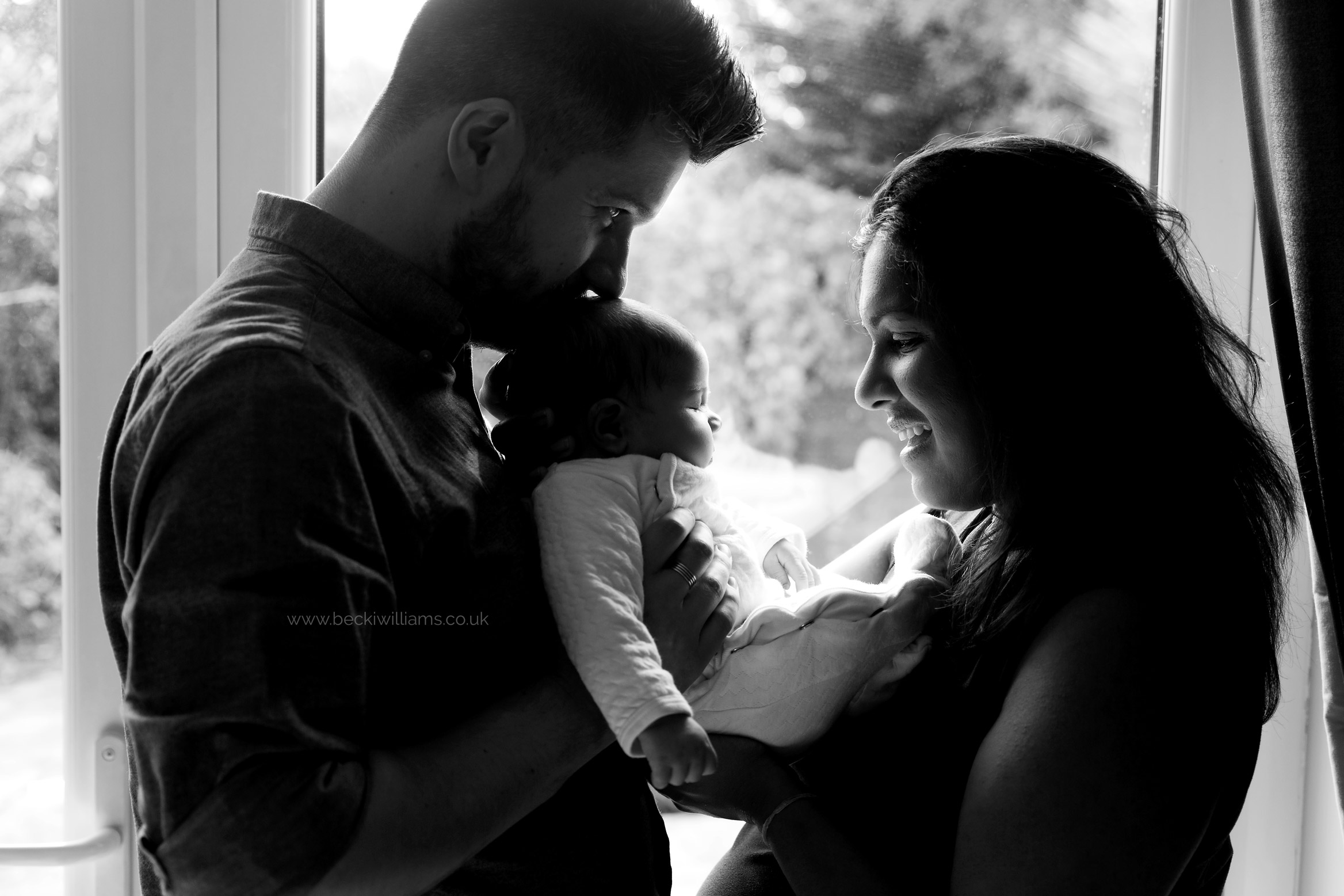 new parents stand in front of a window holding their newborn baby girl between them