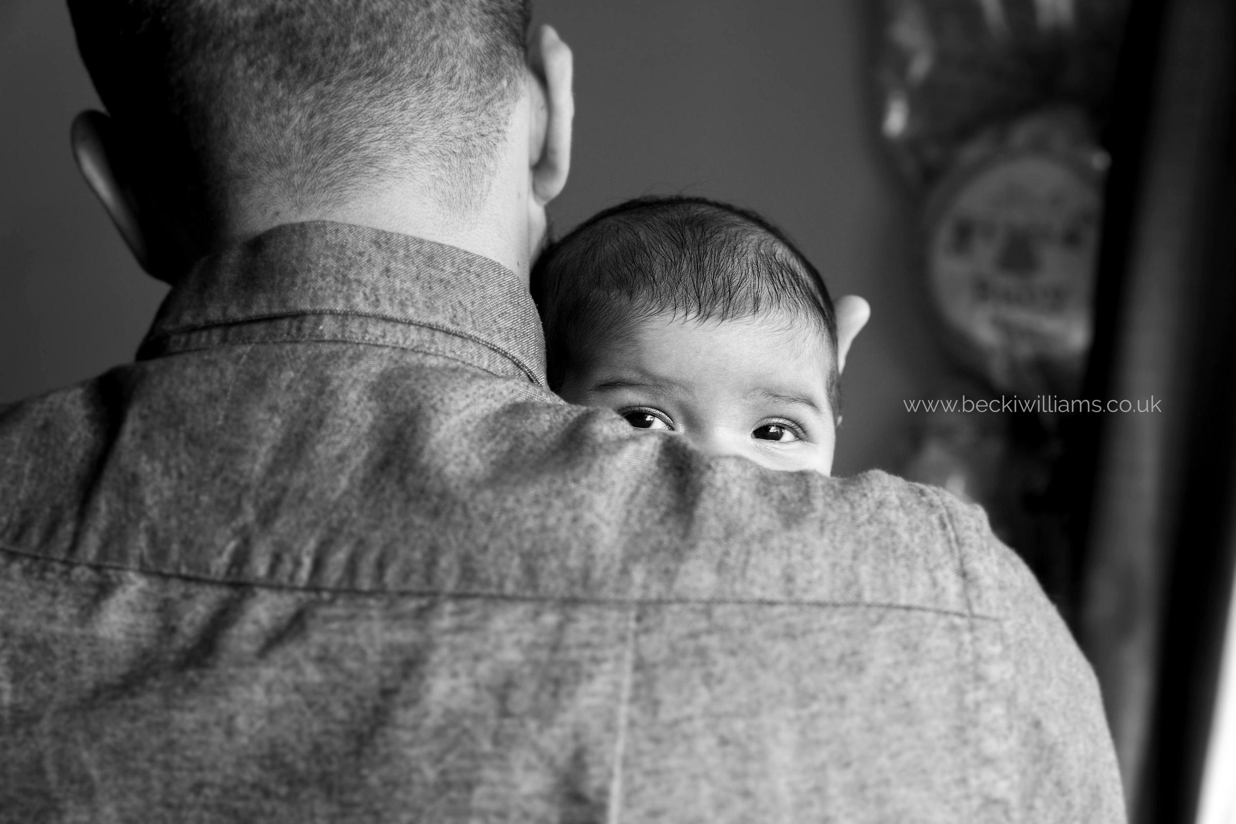 newborn baby girl peeks over her dadies shoulder in black and white