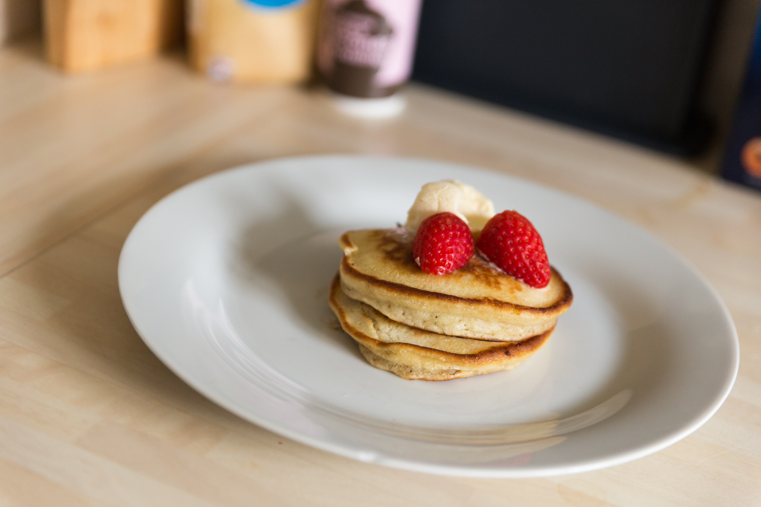 Three american style pancakes on a white plate with ice cream and strawberries on top.