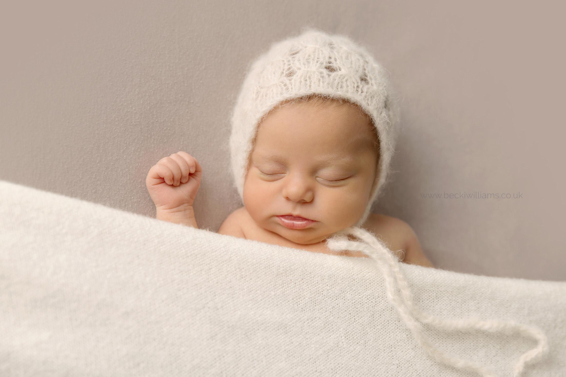 newborn girl asleep under a cream blanket wearing a cream bonnet