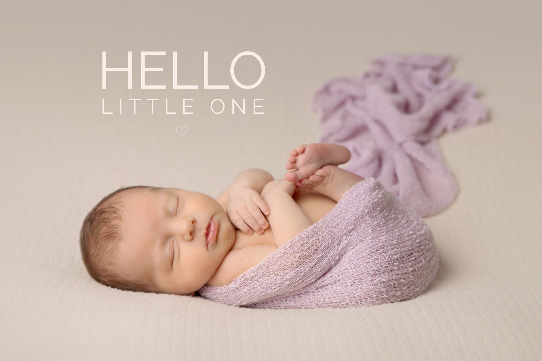 newborn girl laying sleeping on her back wrapped in a pink wrap on a cream blanket.  'hello little one' written in text on the image