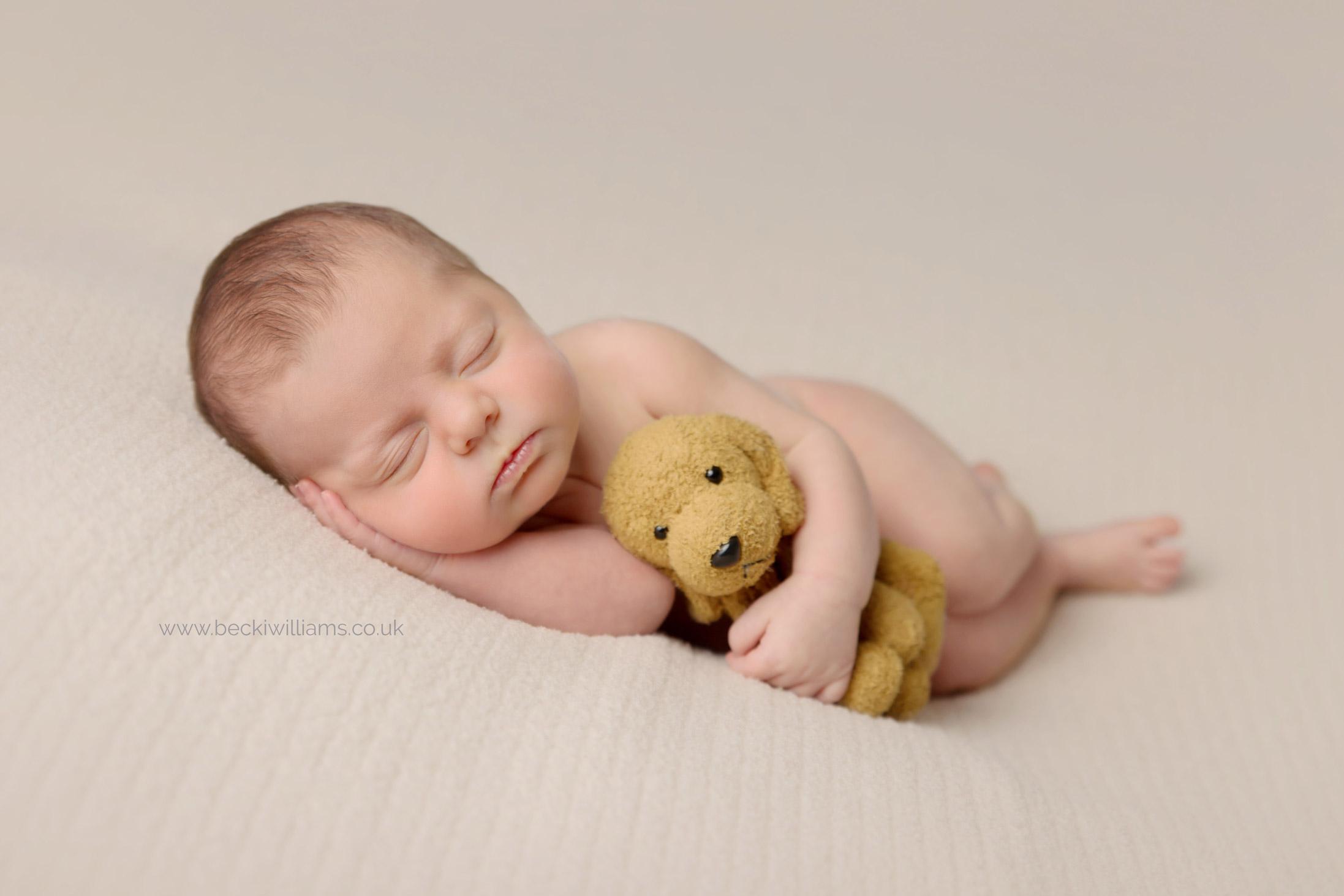 newborn girl laying asleep on her side cuddling a toy dog.