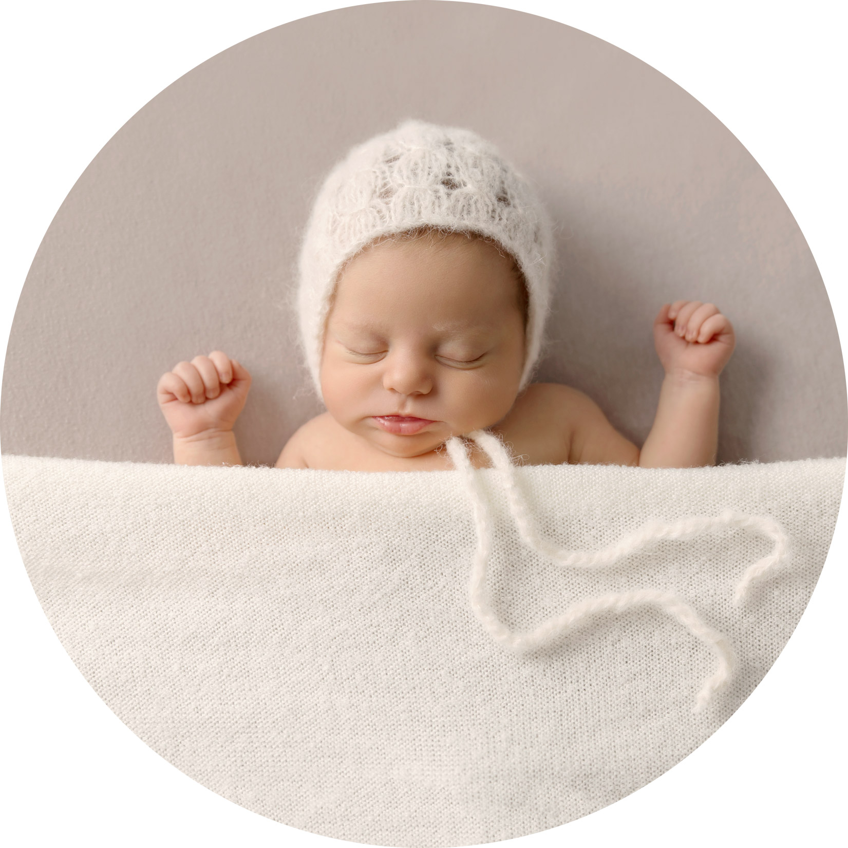 newborn girl laying on her back covered in a cream blanket and wearing a cream bonnet