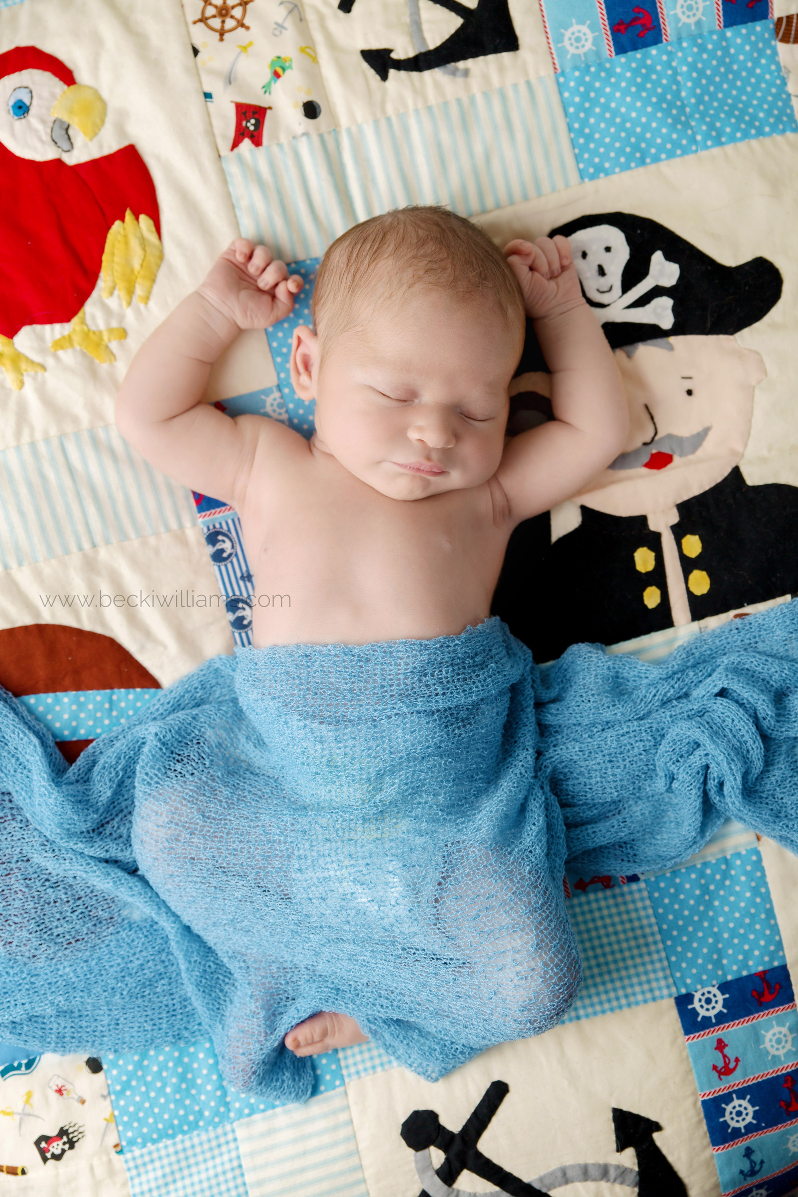 natural newborn photo of a baby laying on a pirate themed quilt, covered in a blue blanket