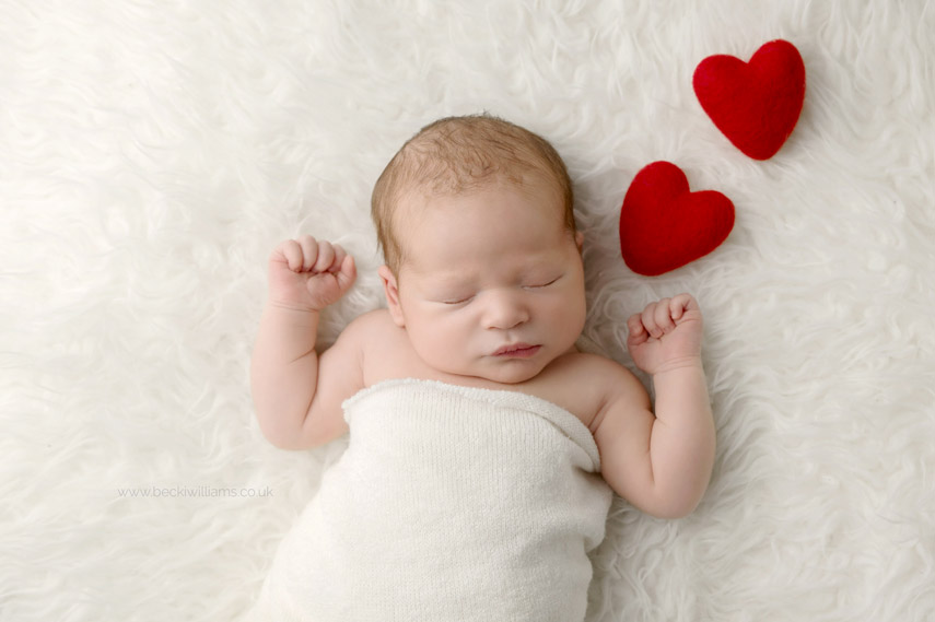 Natural newborn photo of baby boy wrapped in a cream blanket with two red love hearts by his head as if he is dreaming of love